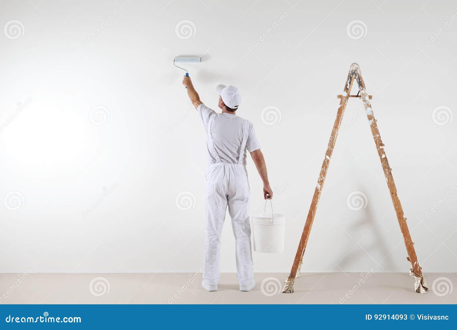 Bakre sikt av målaremannen som målar väggen, med den målarfärgrullen