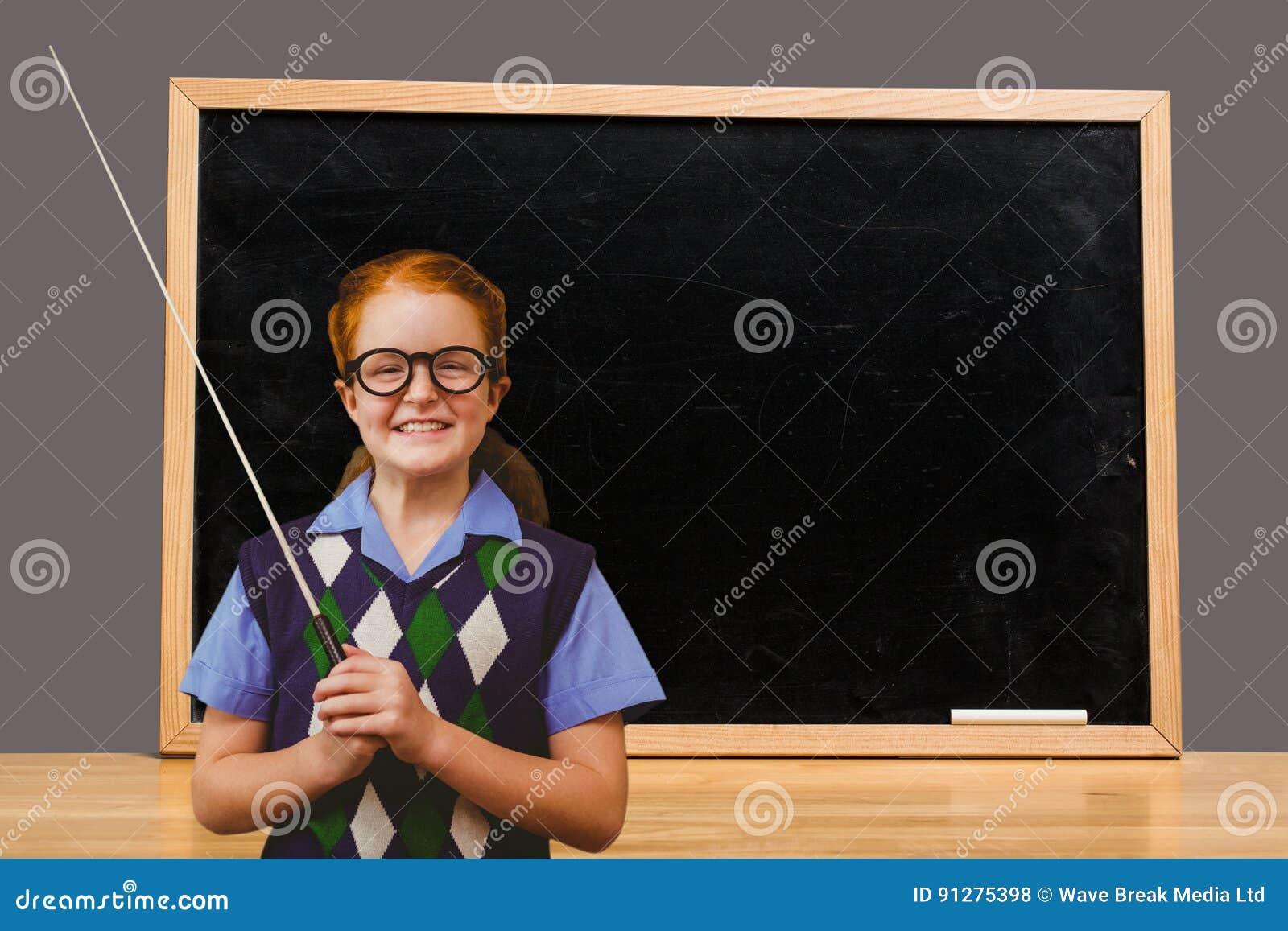 Bakre sikt av skolflickahandstil på den svart tavlan