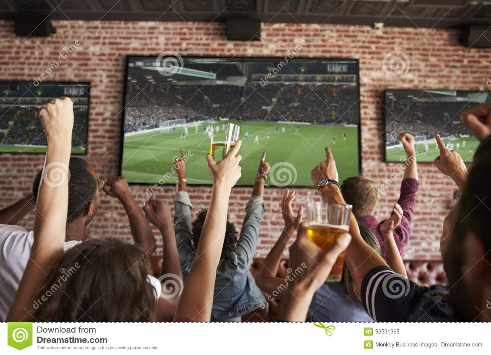 Bakre sikt av vänner som håller ögonen på leken i sportstång på skärmar