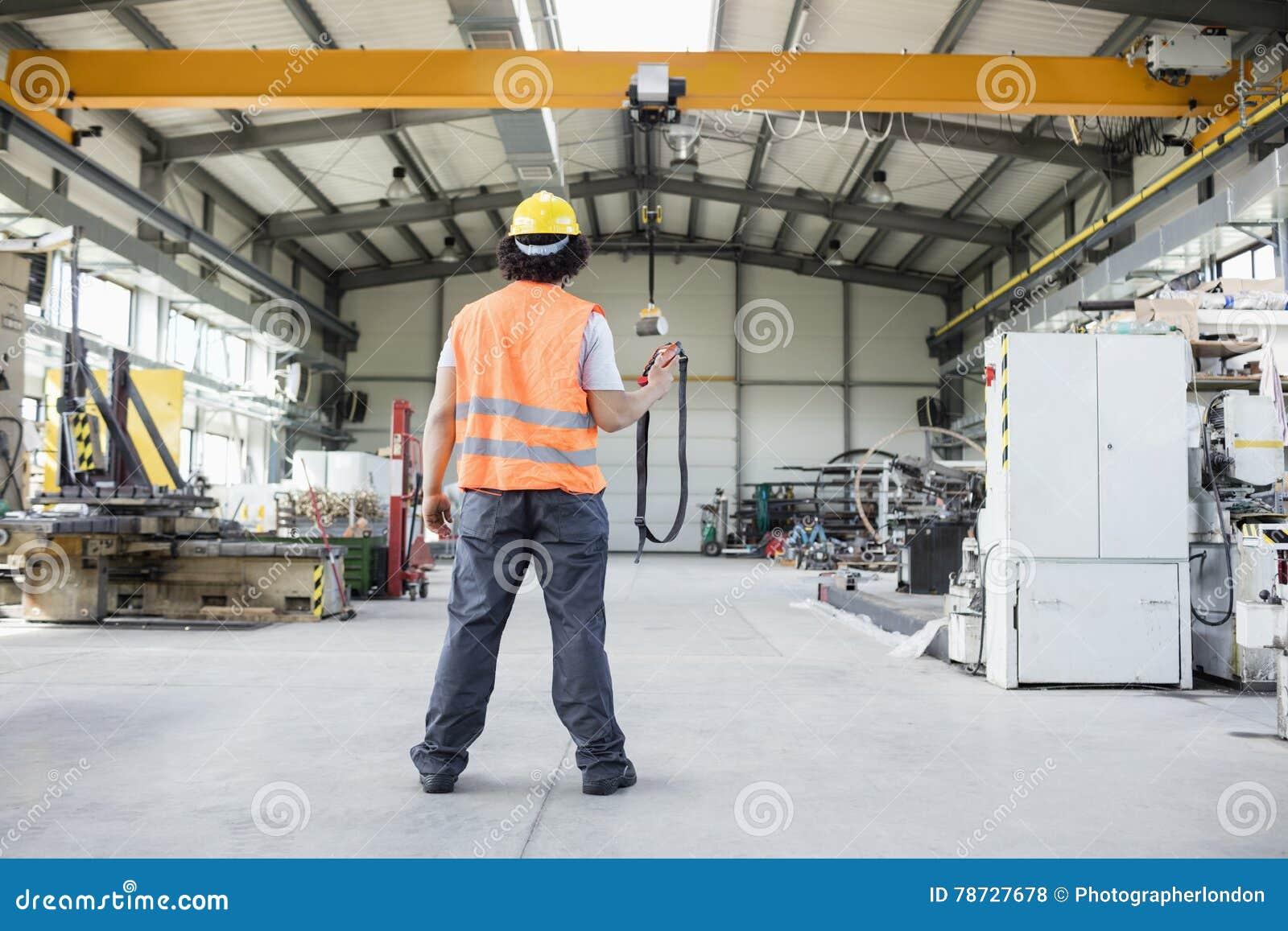 Bakre sikt för full längd av den unga fungeringskranen för manuell arbetare i fabrik