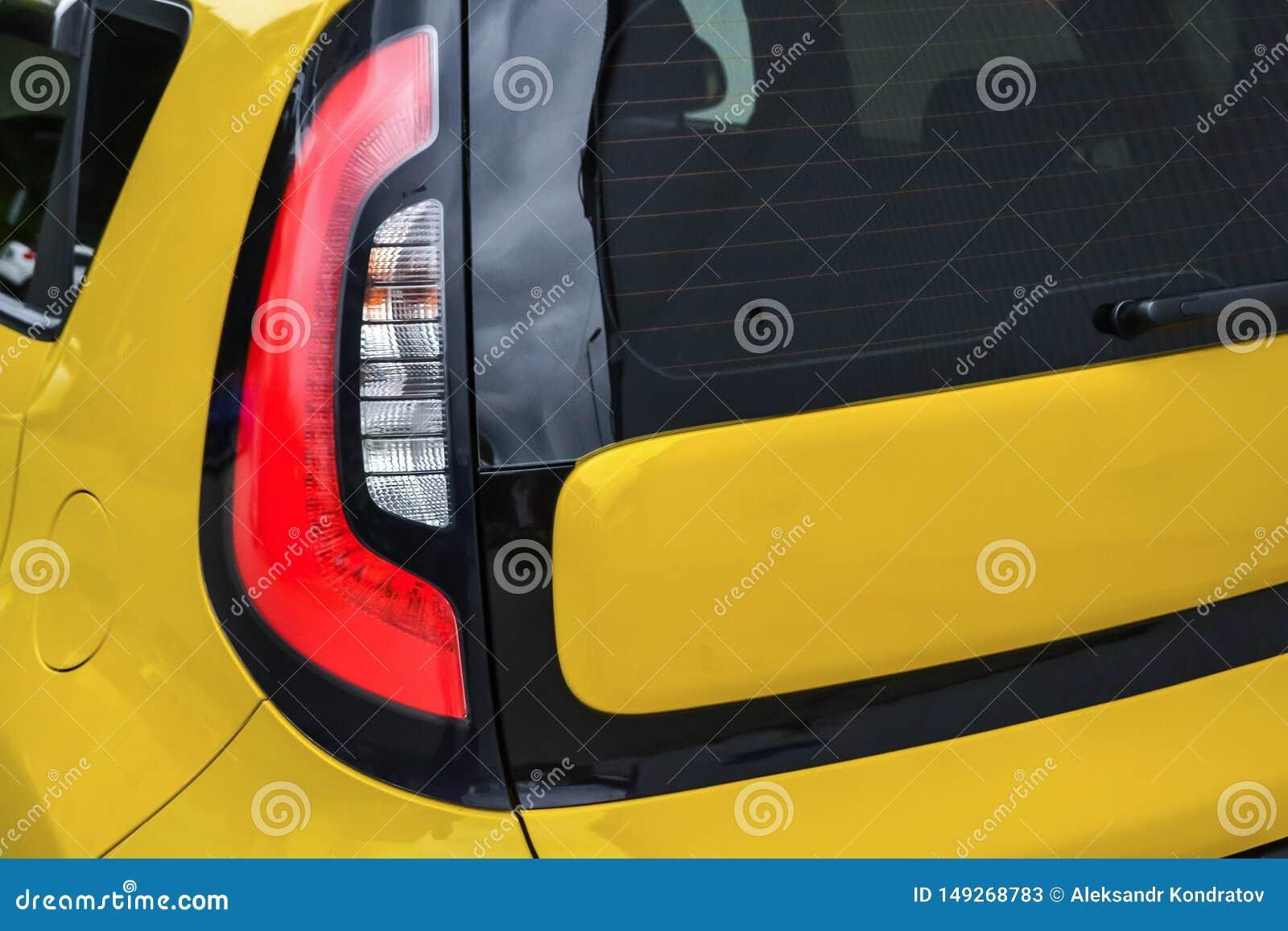 Bakre taillampsikt av den anv?nda bilen i gul f?rg, n?r att ha gjort ren f?r den inday f?rs?ljningen