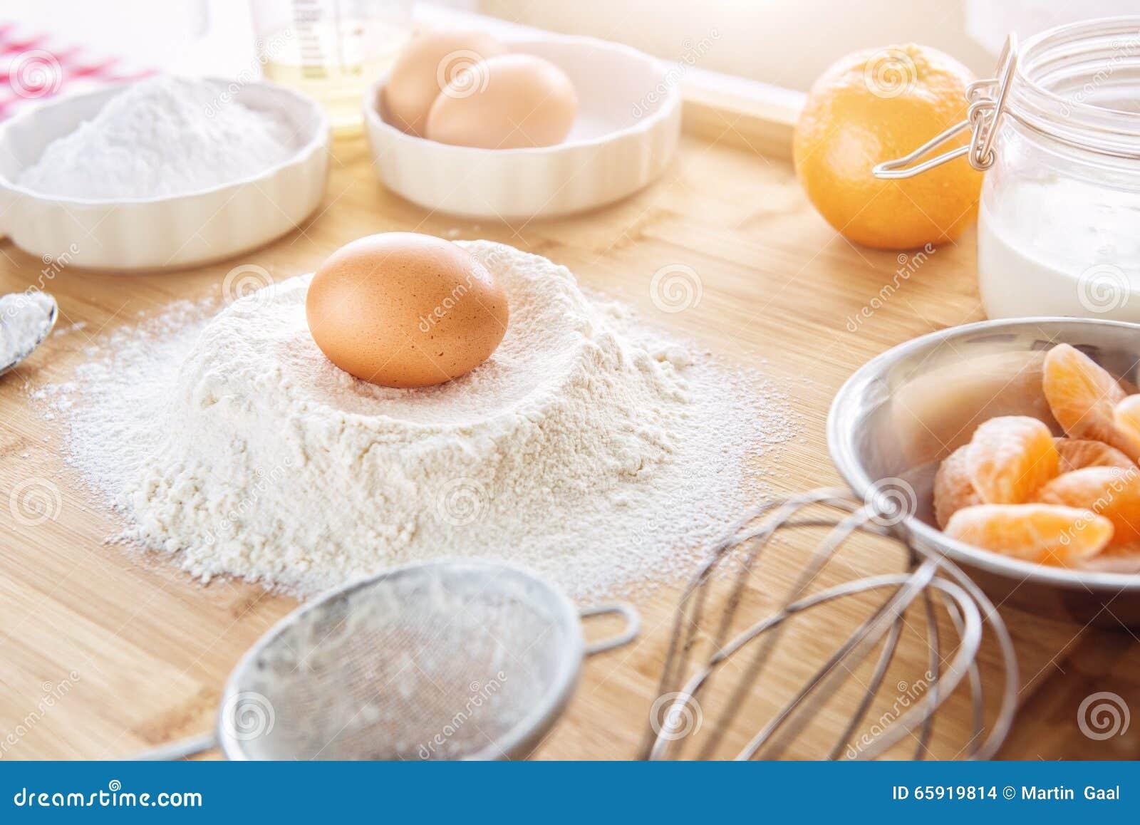 Bakselcake in keuken - de ingrediënten van het deegrecept met fruit op houten lijst