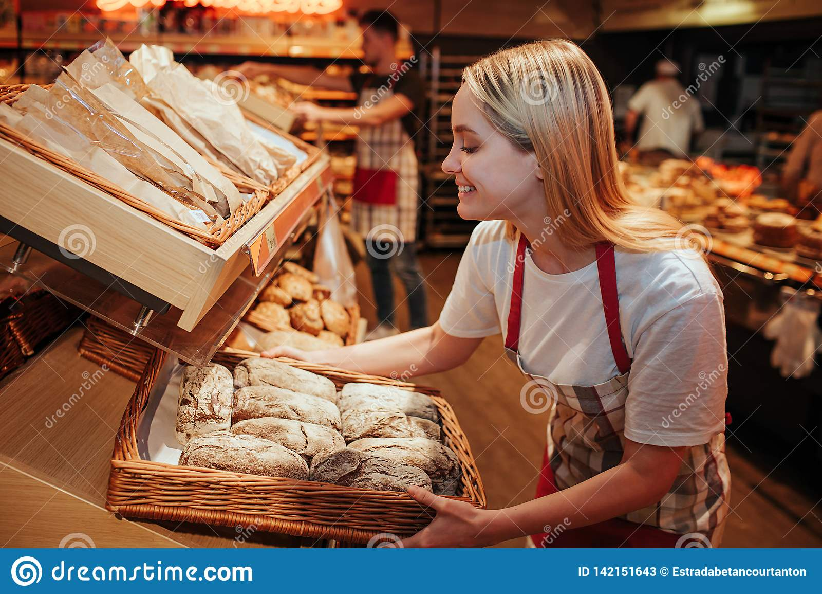 Bakset Griff der jungen Frau mit frischem Brot im Gemischtwarenladen Sie setzte es auf Regal und Lächeln Geschmackvoll und delisi