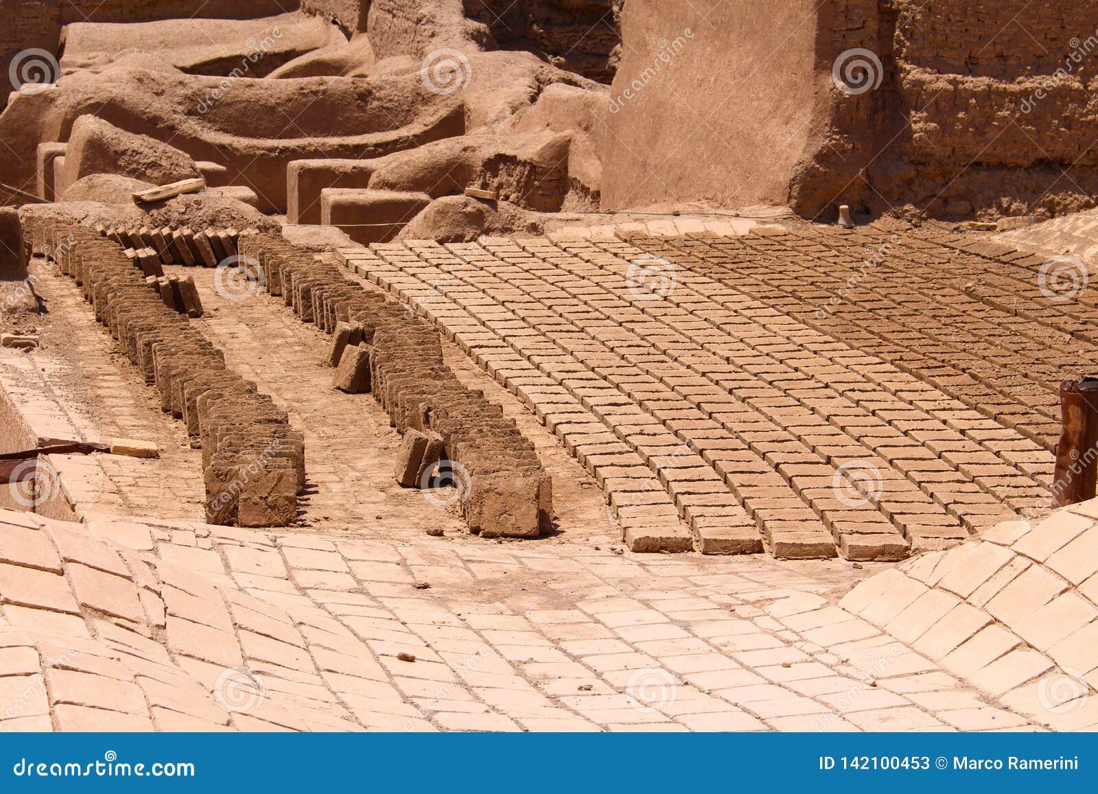 Bakstenen in de zon in de stad van Rayen, Iran worden gebakken dat