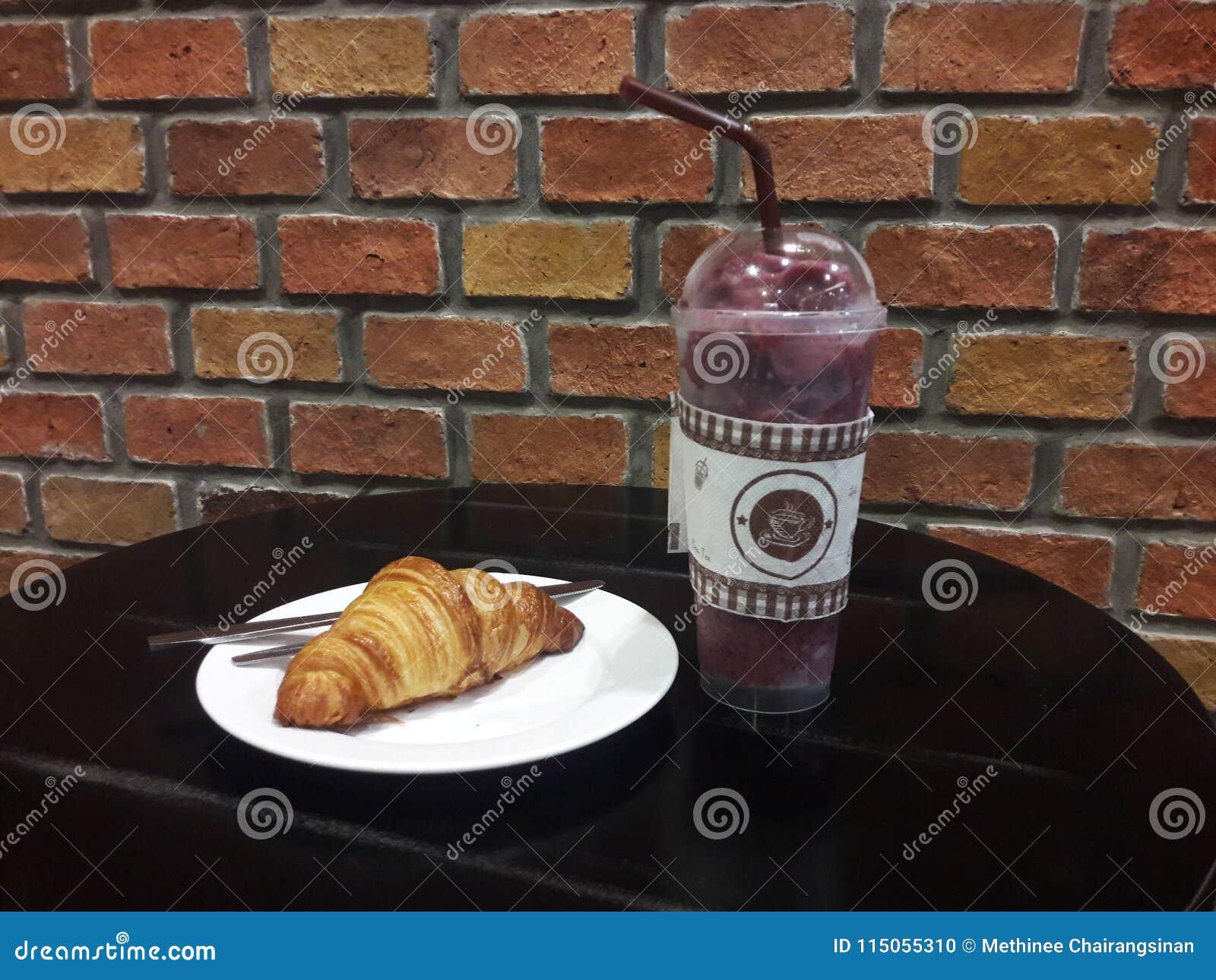 Bakstenen muur en drank en een croissant op lijst