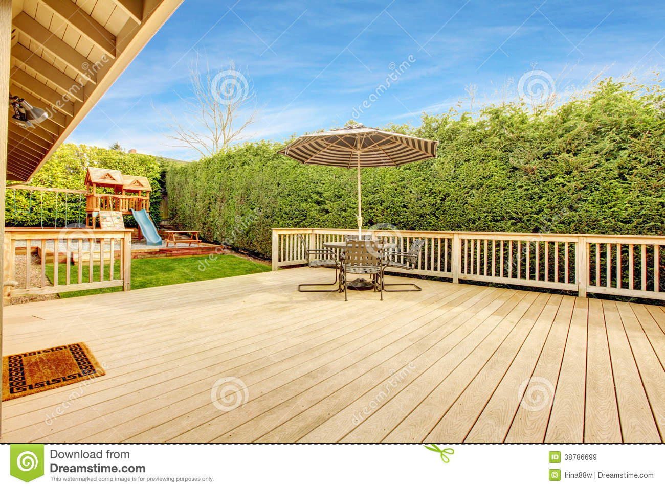Spacious wooden deck with umbrella and patio table set. View of play ...