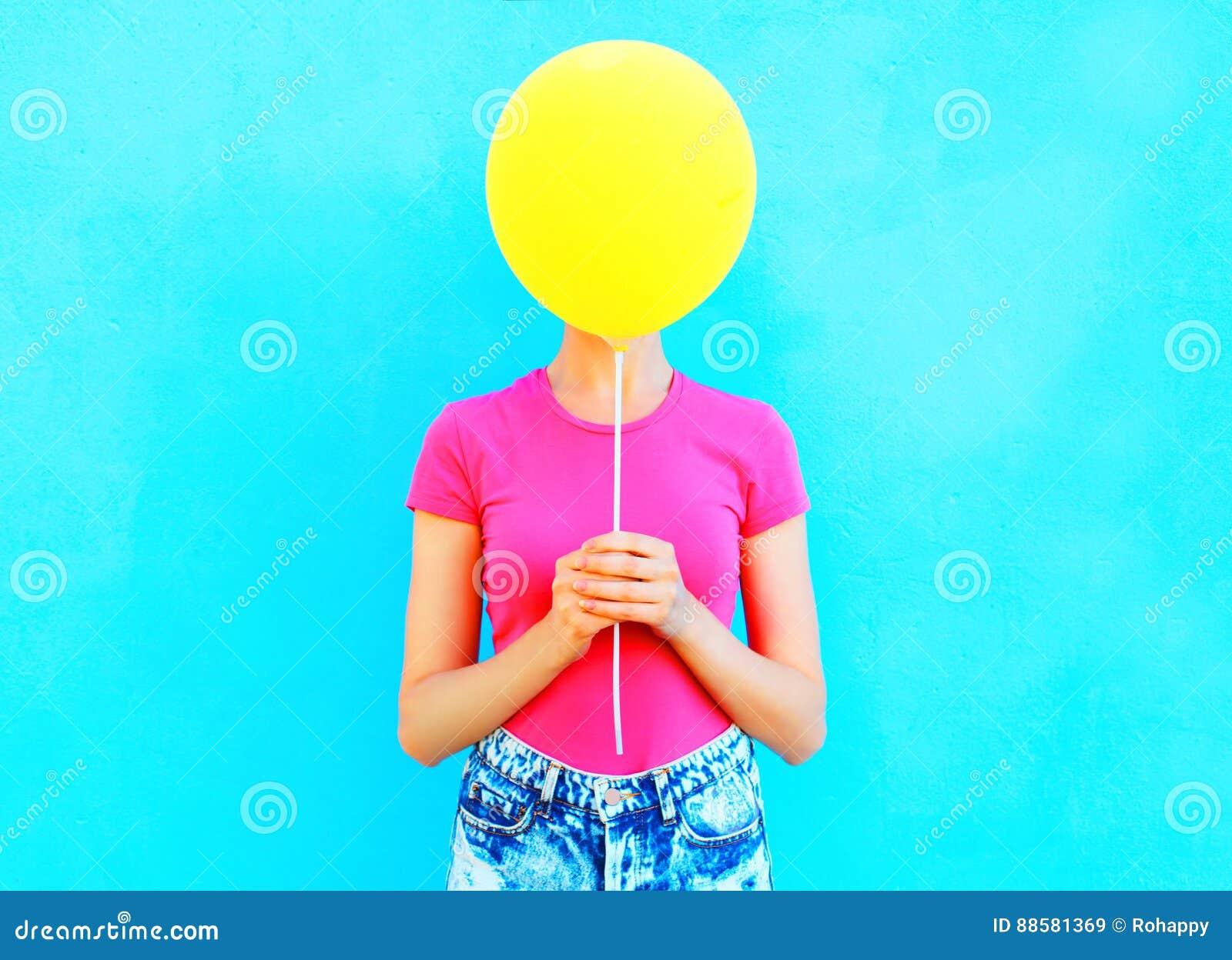Balão de ar amarelo escondendo da cara da mulher olorful do ¡ de Ð que tem o divertimento sobre o azul