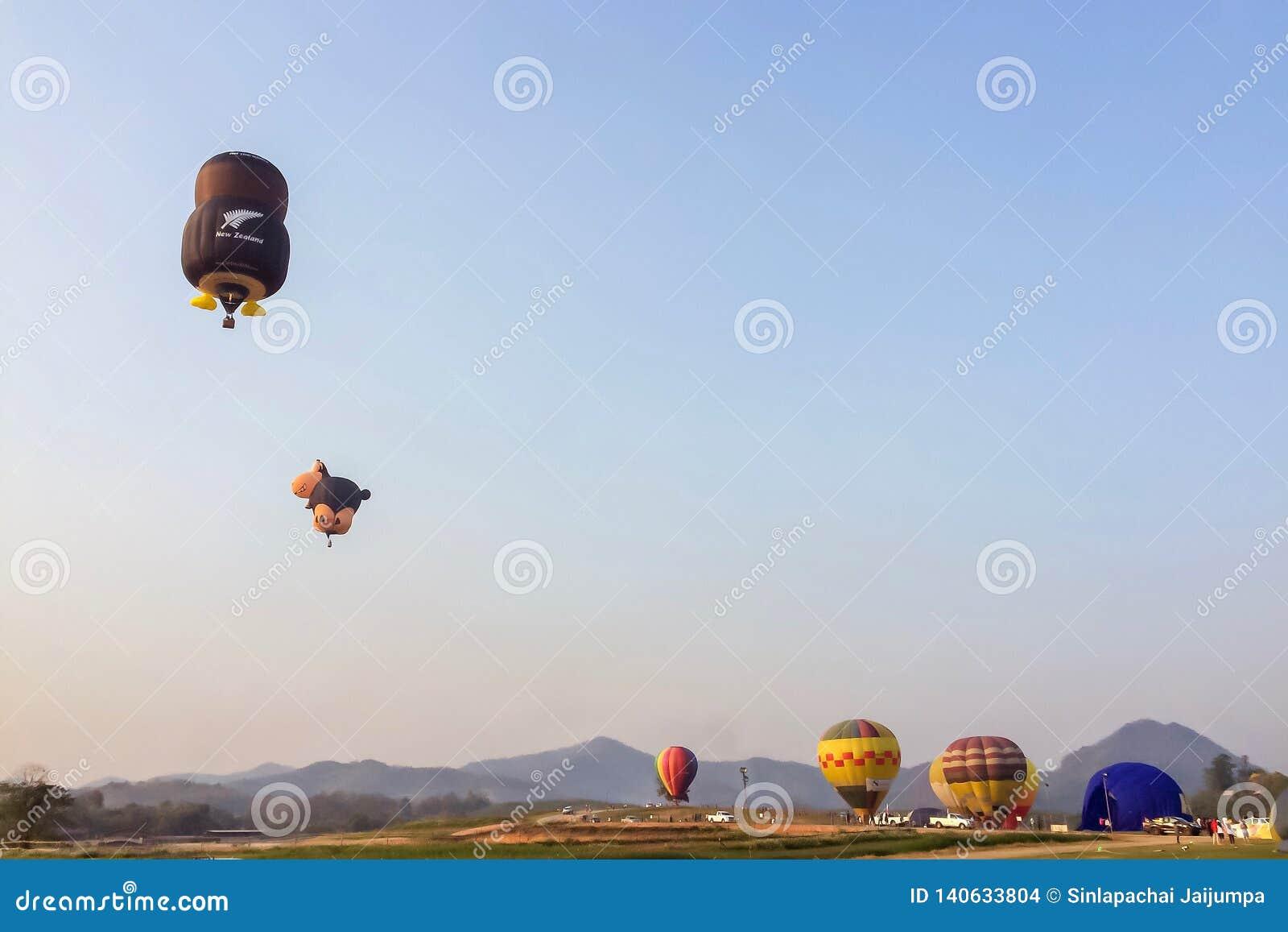 Balão de ar quente colorido que flutua sobre o prado com montanha e o céu azul no parque Chiang Rai International Balloon Fiesta