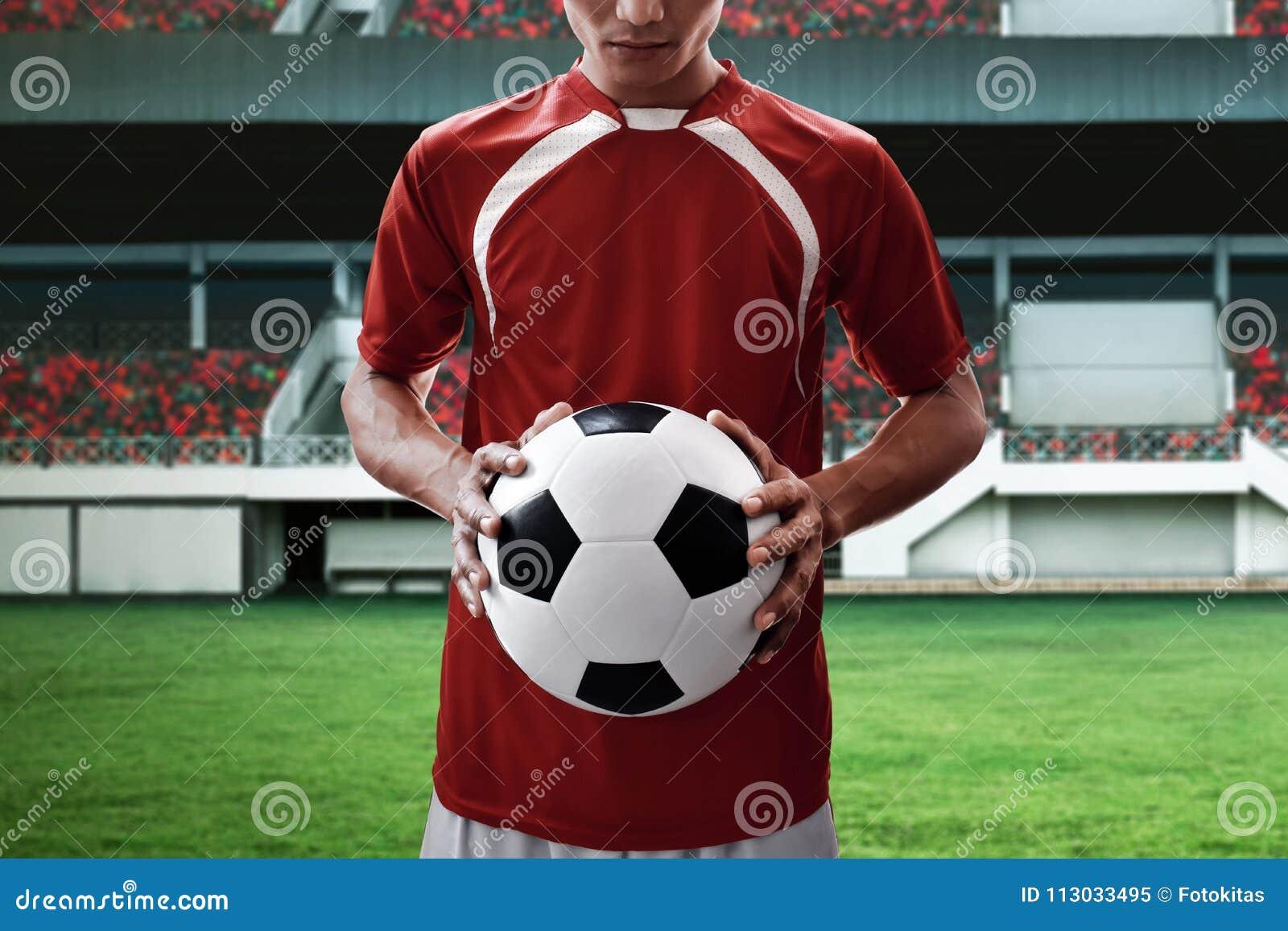Balón de fútbol del control del jugador de fútbol