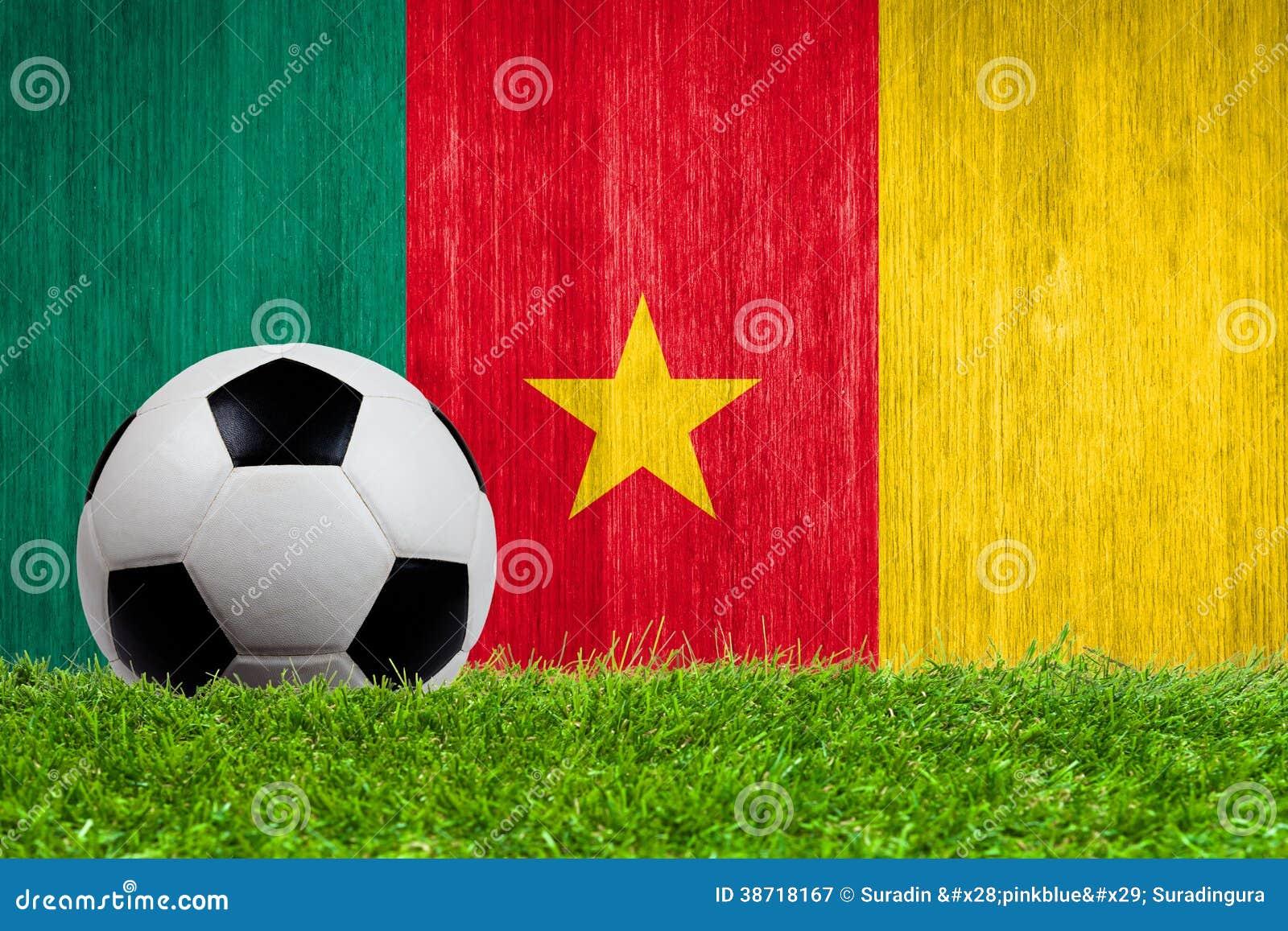 Balón de fútbol en hierba con el fondo de la bandera del Camerún