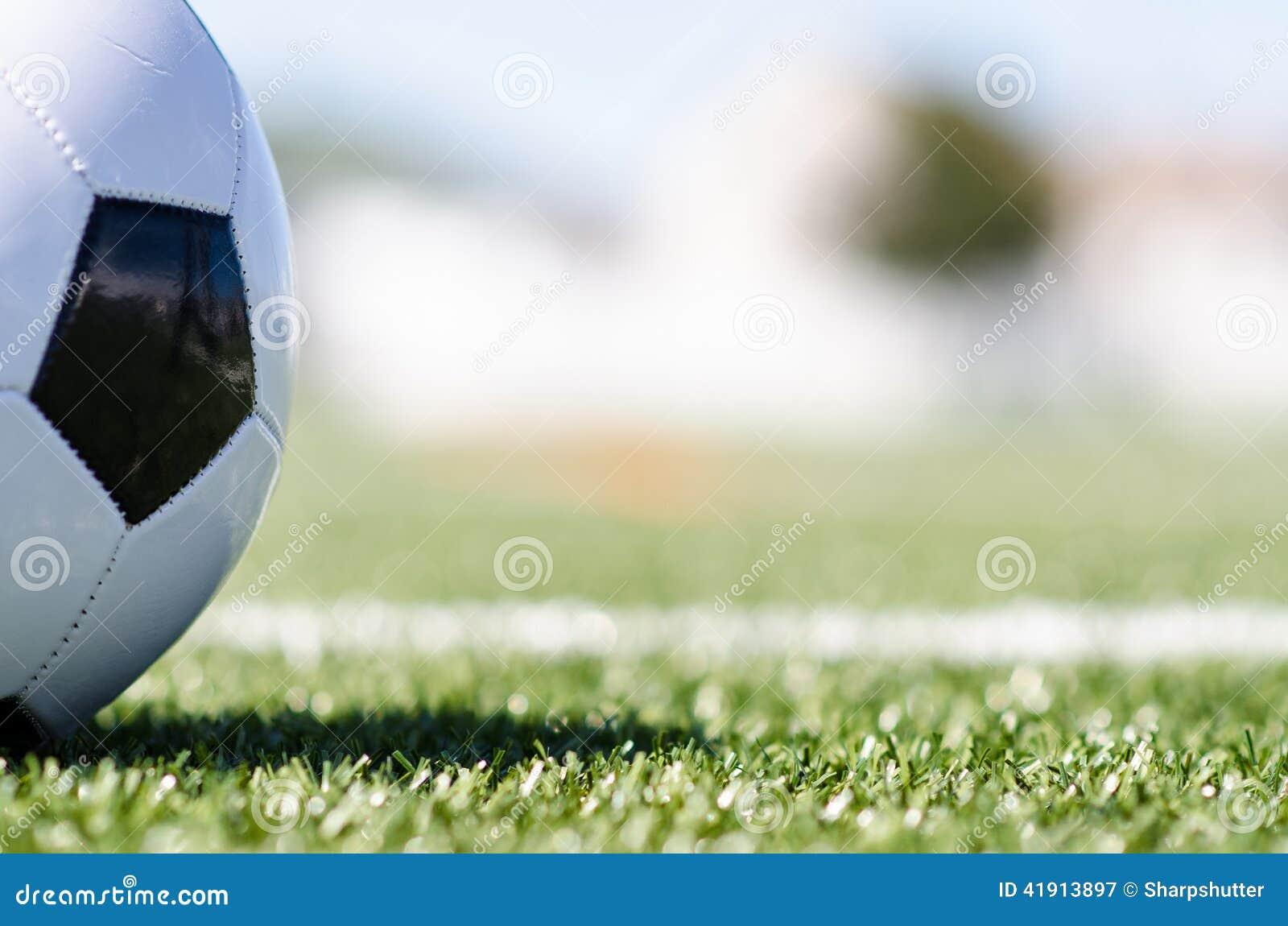 Balón de fútbol en hierba con la sombra