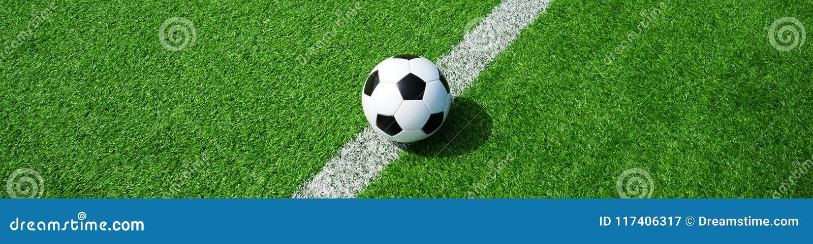 Balón de fútbol en la hierba artificial verde, formato de paisaje, para una bandera