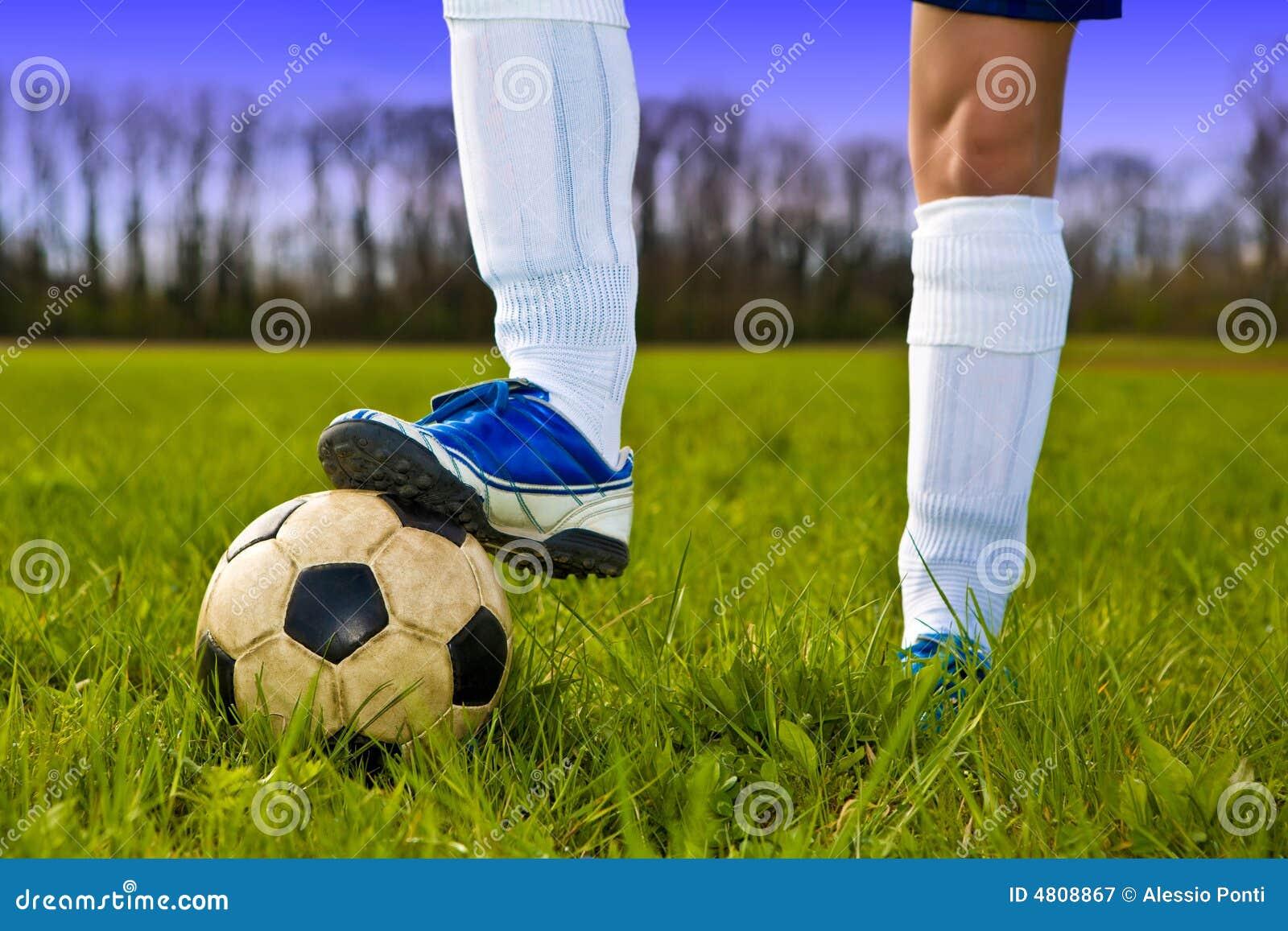 Balón de fútbol y pies del jugador