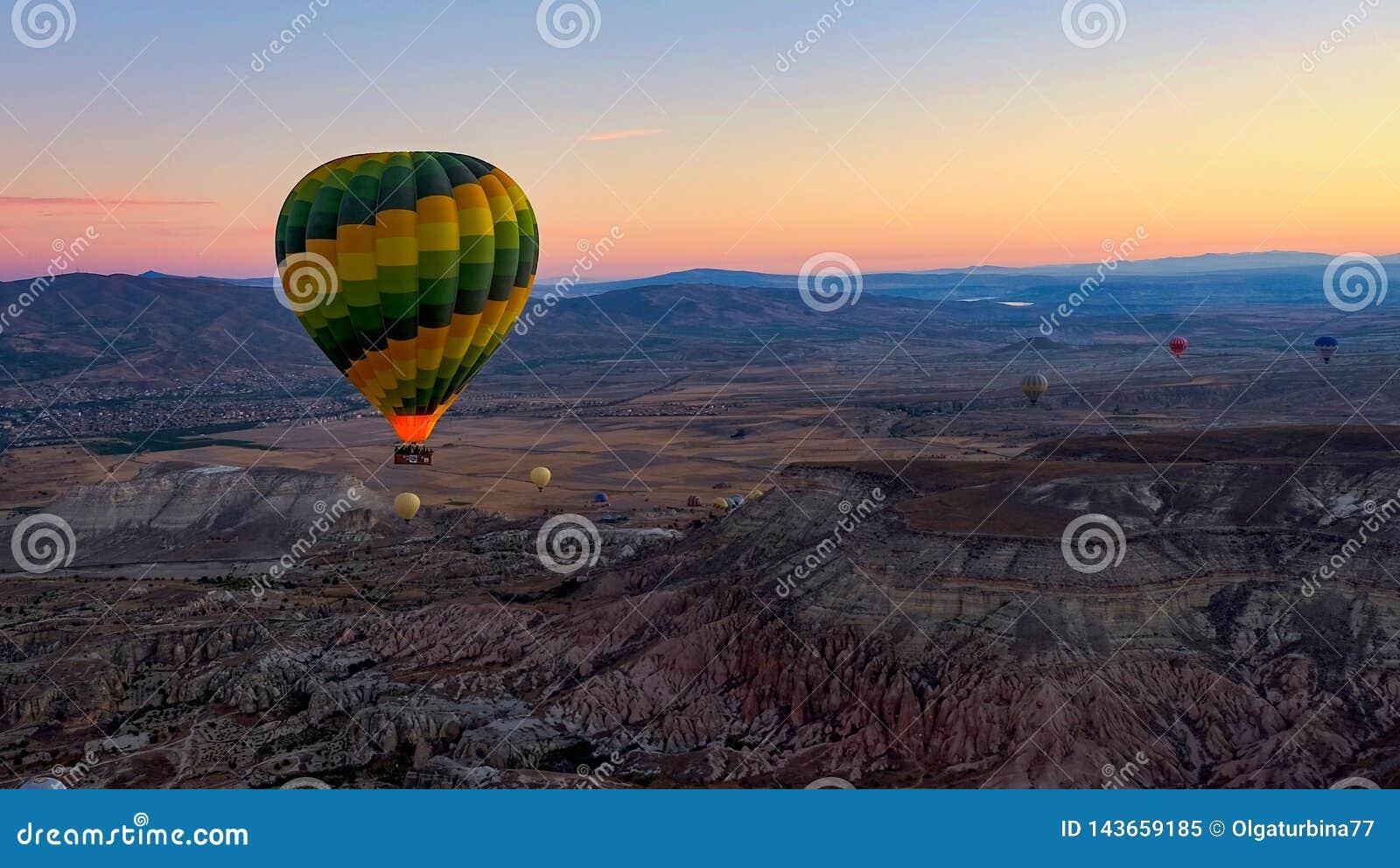 Balões de ar quente coloridos crescentes sobre o vale no nascer do sol Cappadocia, Turquia, outono
