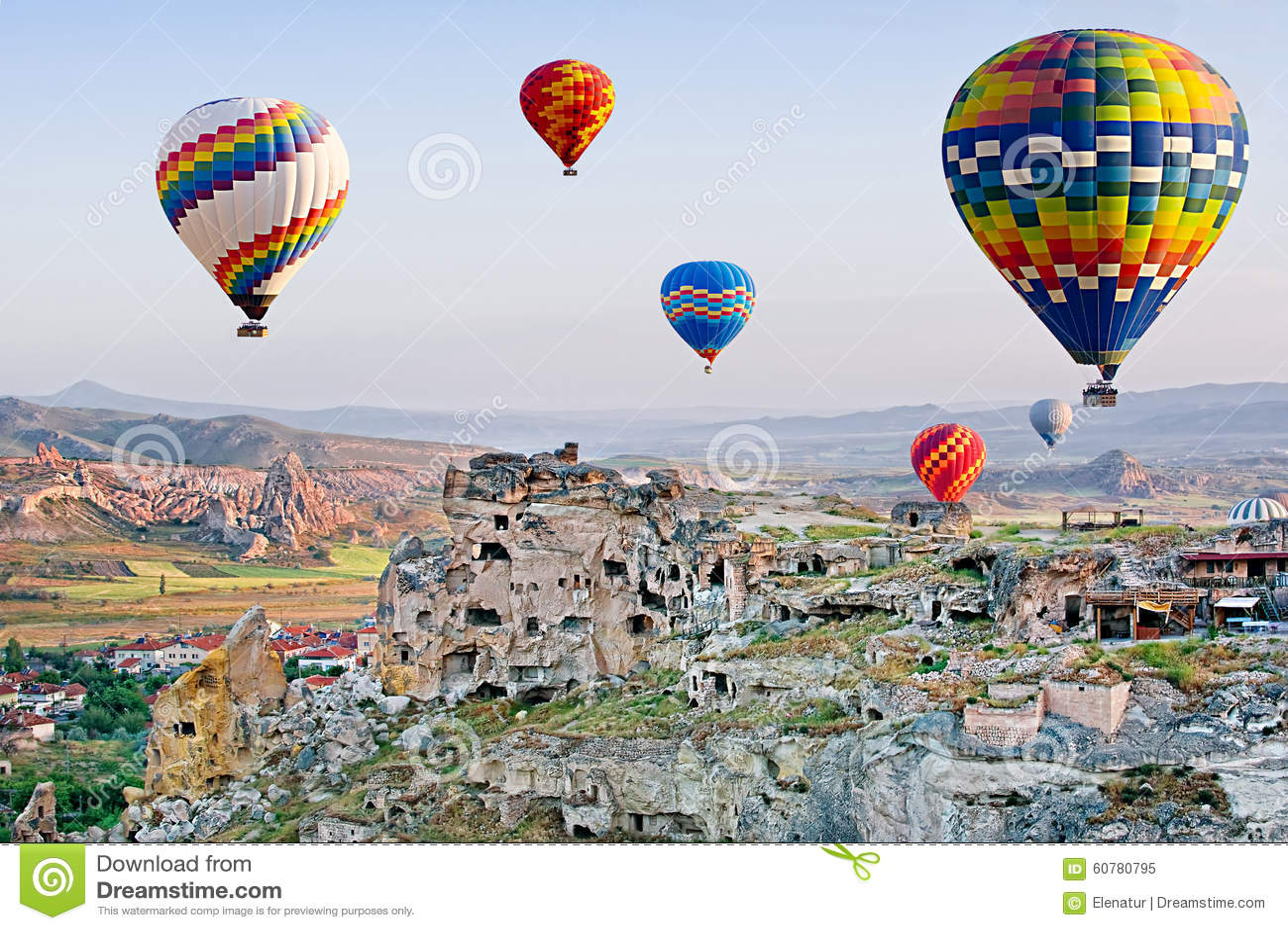 Balões de ar quente coloridos que voam sobre Cavusin em Cappadocia