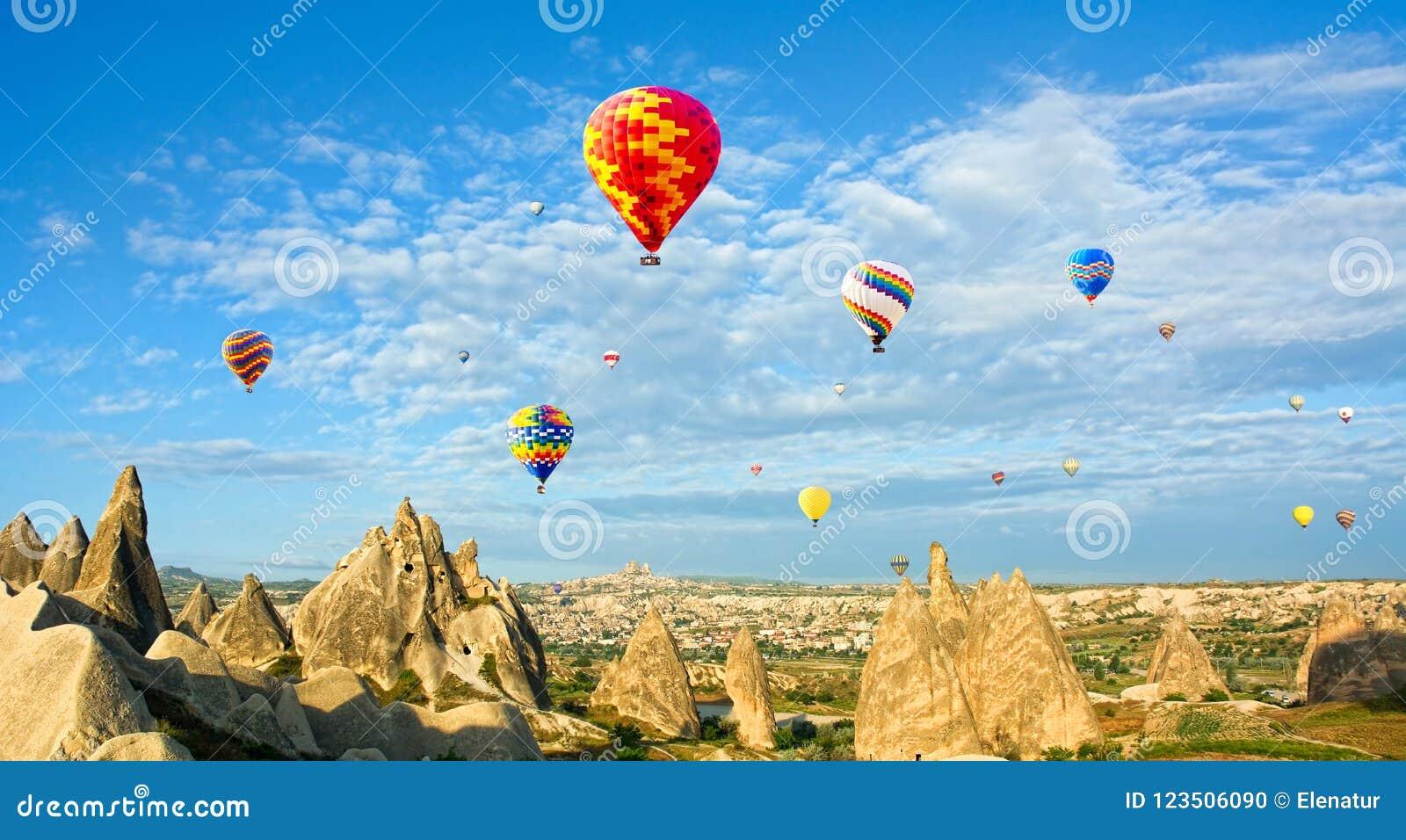 Balões de ar quente coloridos que voam sobre penhascos vulcânicos em Cappado