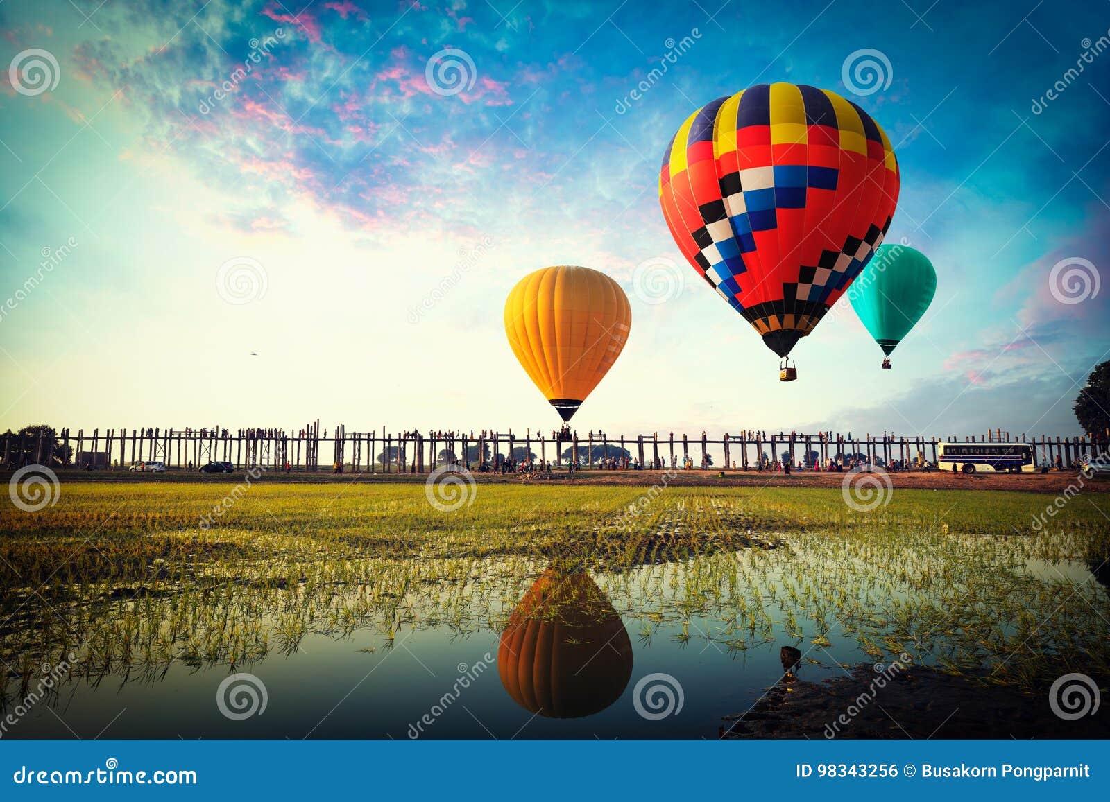Balões de ar quente coloridos que voam sobre a ponte do u-bein em Burma