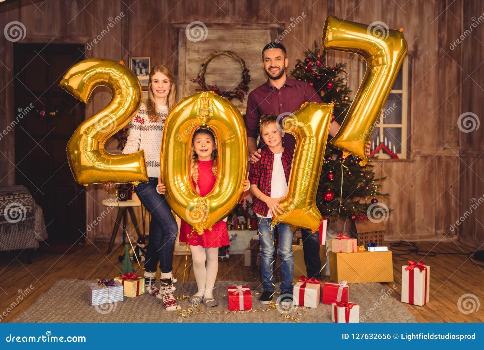 Balões dourados e vista do sinal da terra arrendada feliz da família 2017