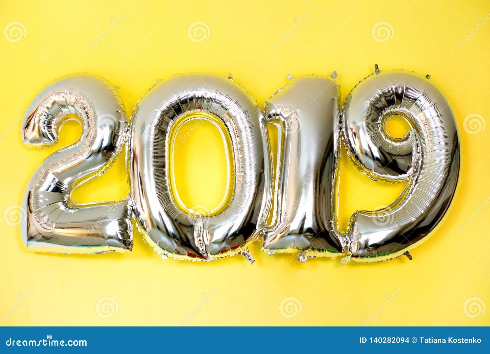 Balões infláveis de prata na forma dos números 2019 no fundo amarelo