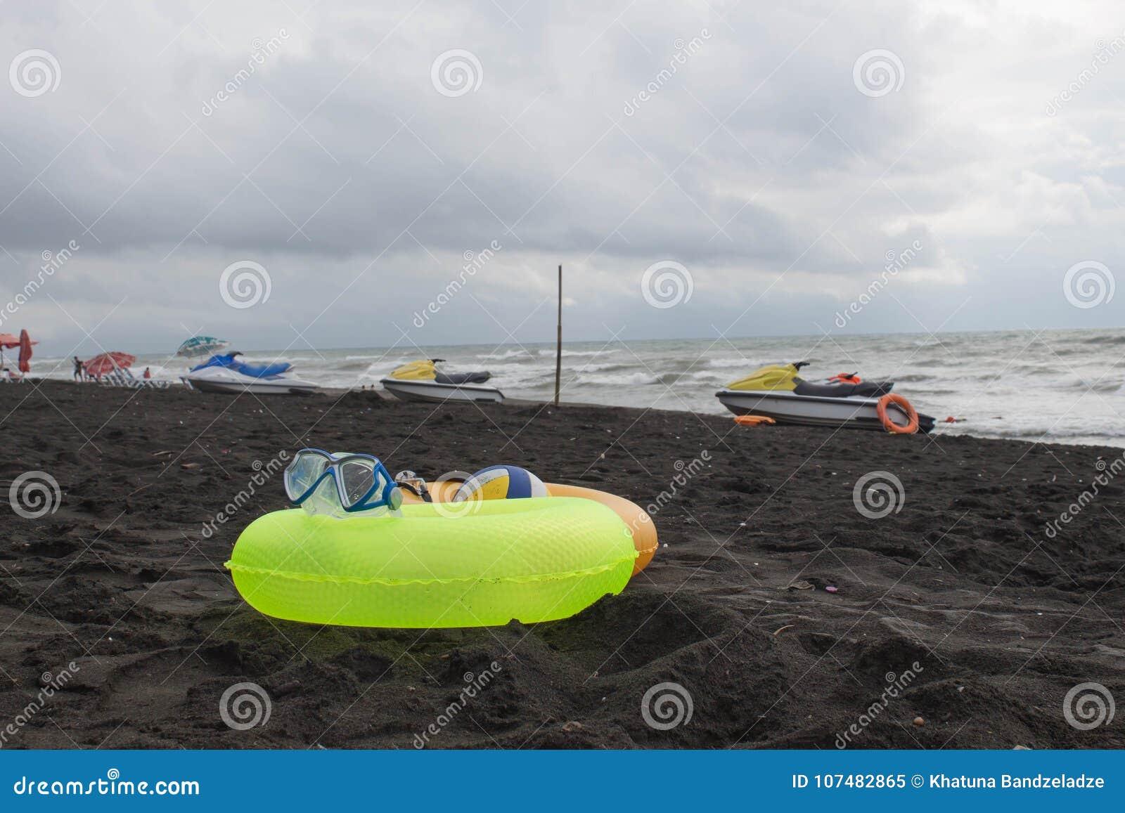 Bal, zwemmende glazen, Waterautoped en Drijvende Ring twee op strand Vage mensen op zandstrand Reis of overzeese vakanties concep
