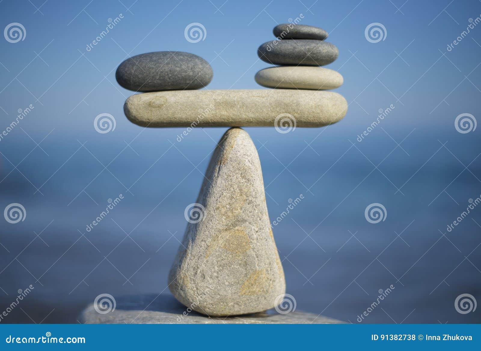 Balance stenar Att att väga för- och nackdelar Balansera stenar på överkanten av stenblocket close upp