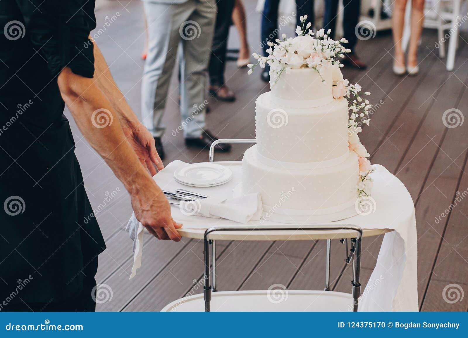 Balanceo del camarero en pastel de bodas blanco asombroso con las flores moder