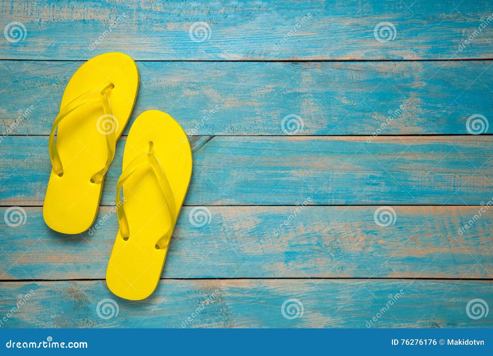 Balanceo, sandalia, verano Sandalias amarillas de la chancleta en la madera azul