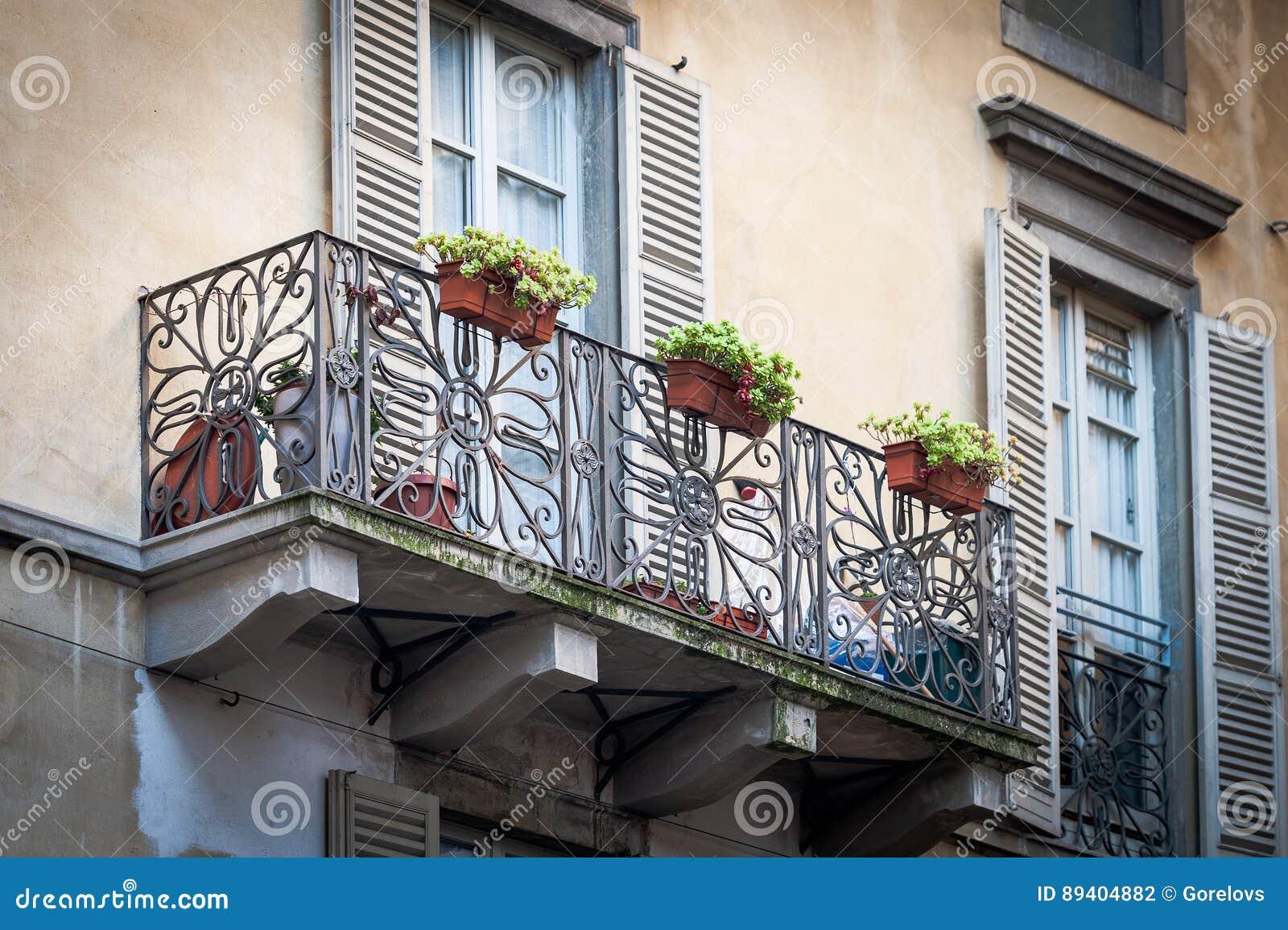Balcão italiano tradicional com os potenciômetros de flor na cidade de Bergamo, Itália