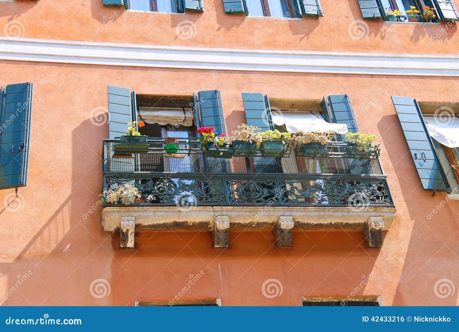 Balcón pintoresco con las flores en una casa vieja