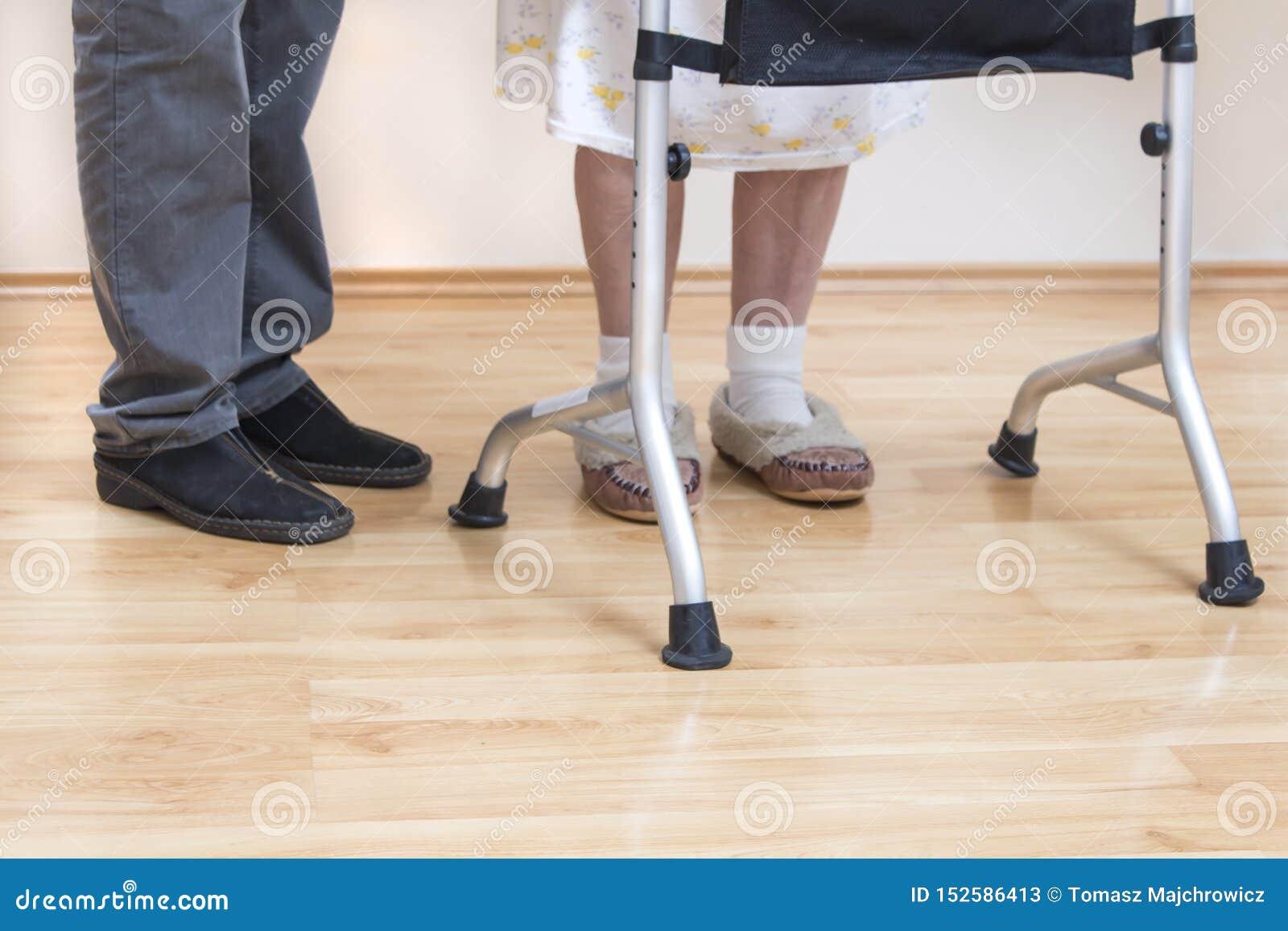 Balconi medici di riabilitazione La nonna impara camminare con l aiuto di un camminatore ed assistito da un infermiere