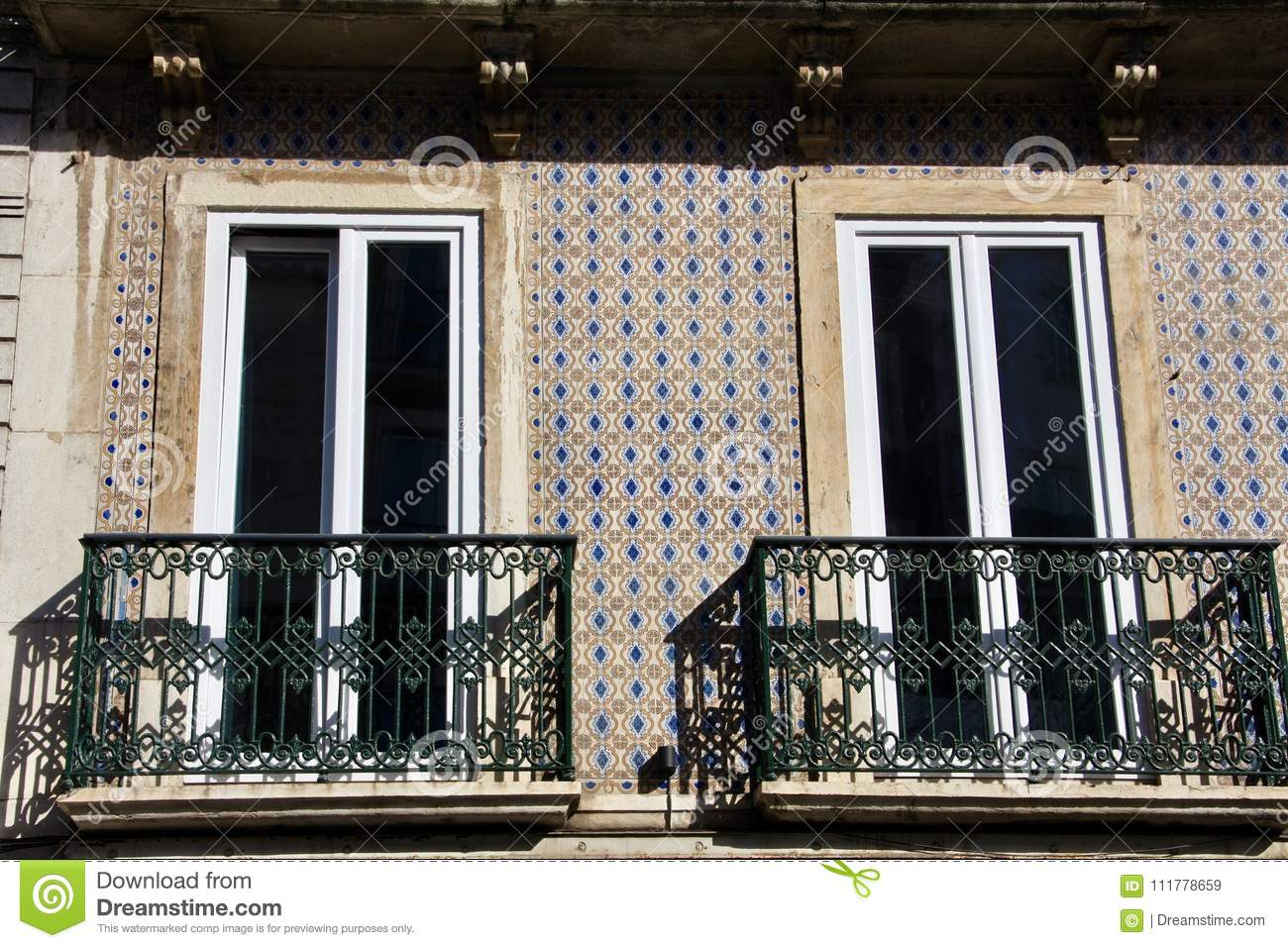 Two balconies on tiled by azulejo facade of building in Lisbon .