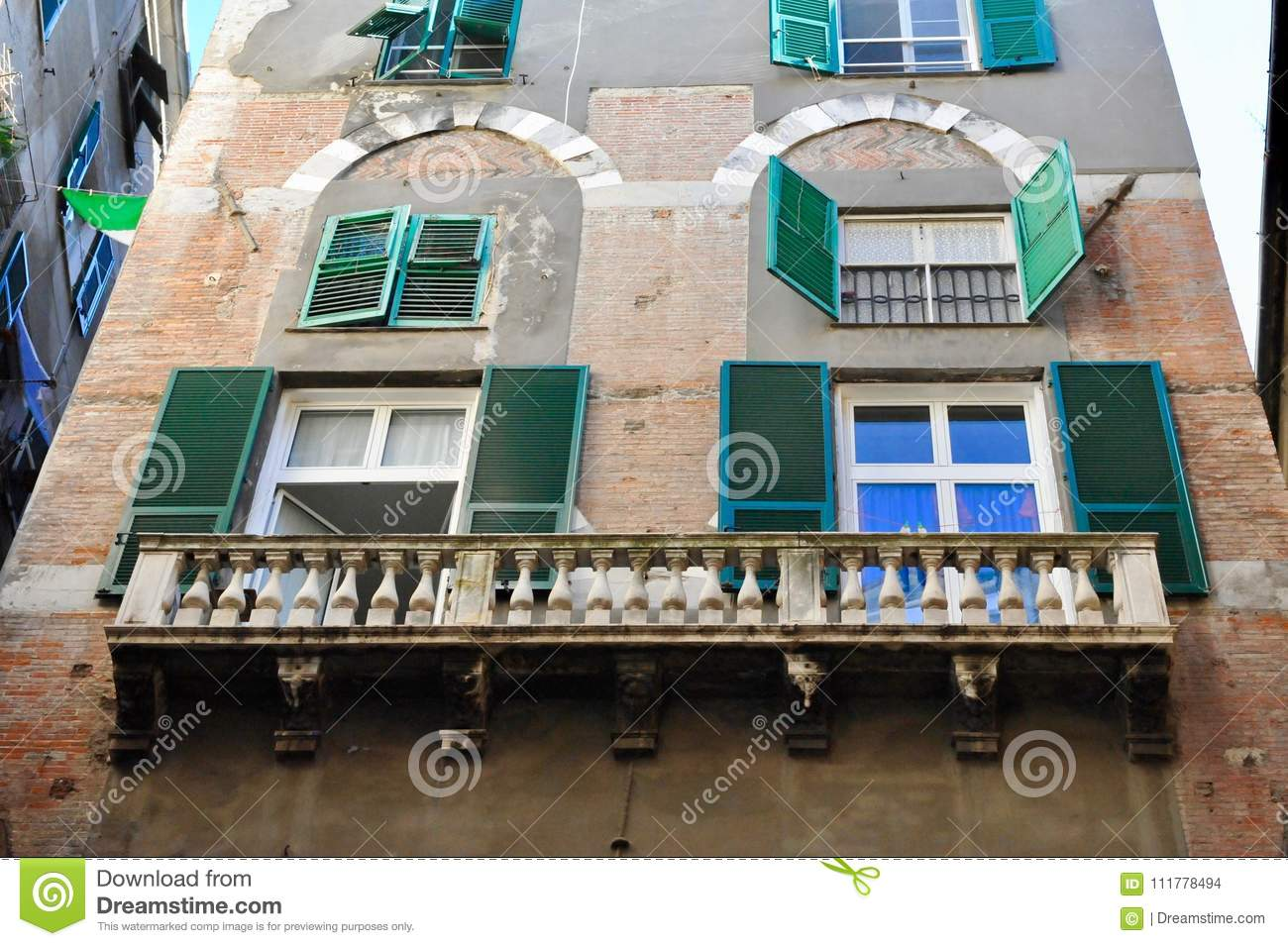 Balconies and windows with green shatters on facade of building in Genova, Italy.