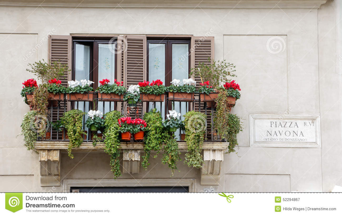 Balcony With Flowers On An Old Yellow Apartment Building In Rome