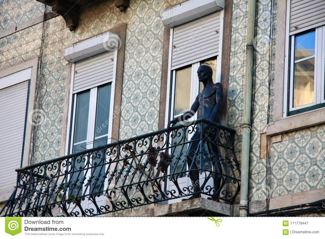 Black standing trade dammy on traditional portugal house balcony.
