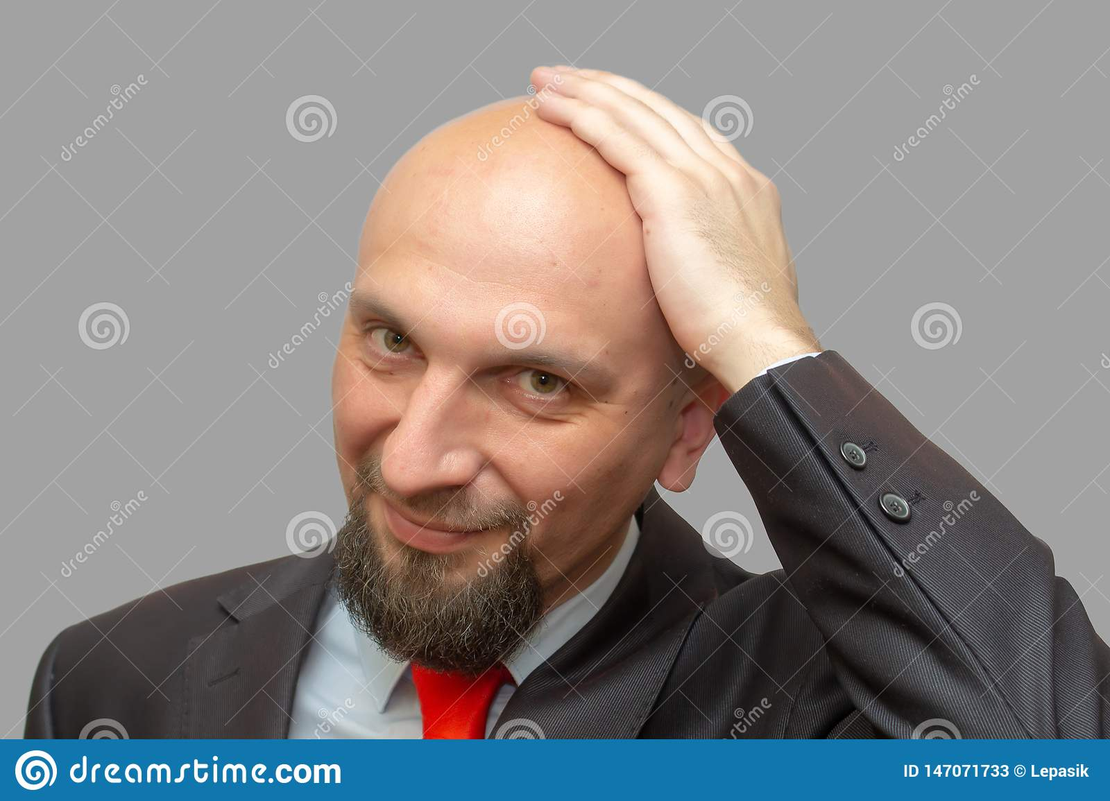 Bald man in suit, shaved head, gray background