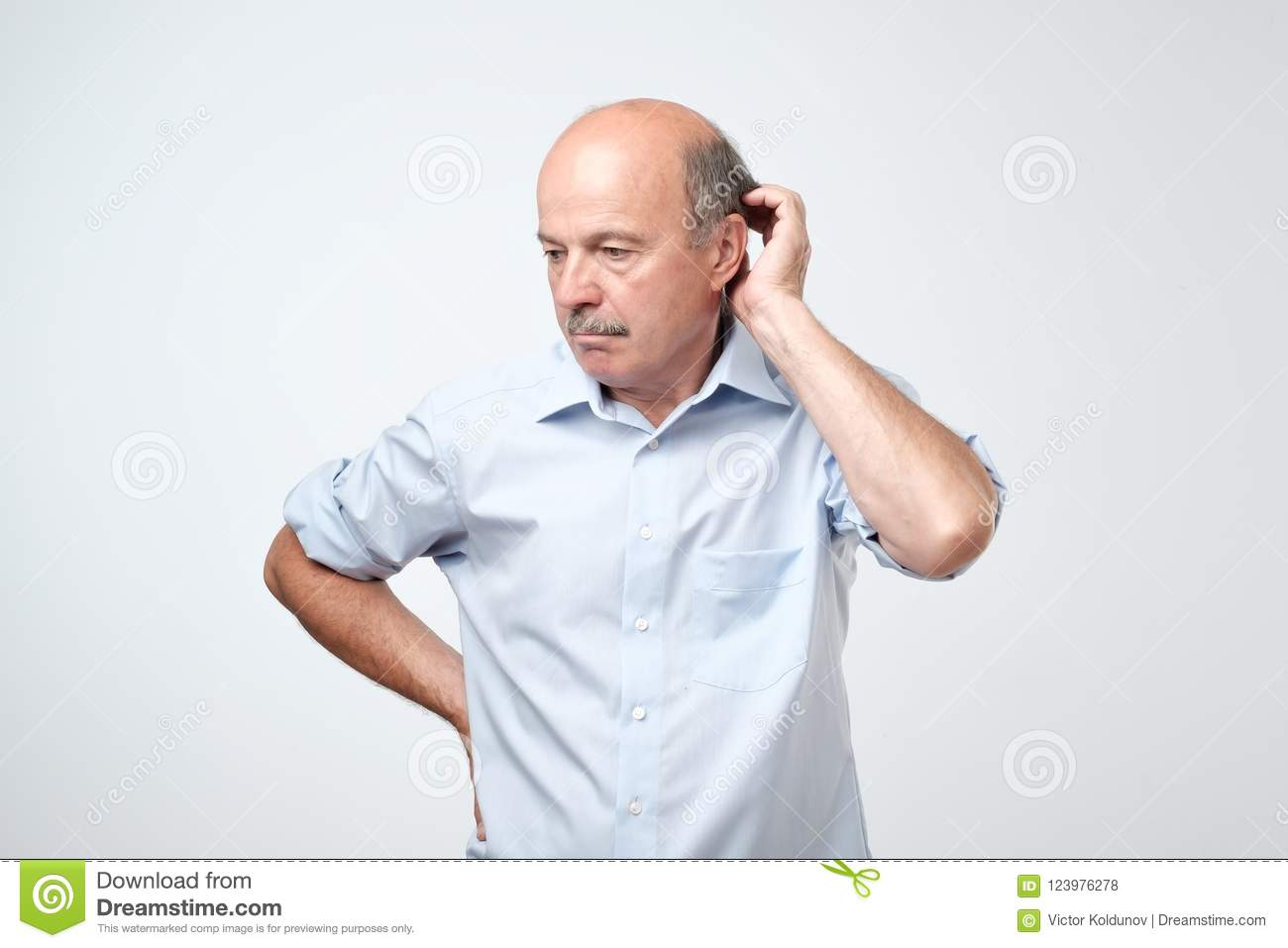 Bald mature man with mustache in blue shirt is suffering from indecision.