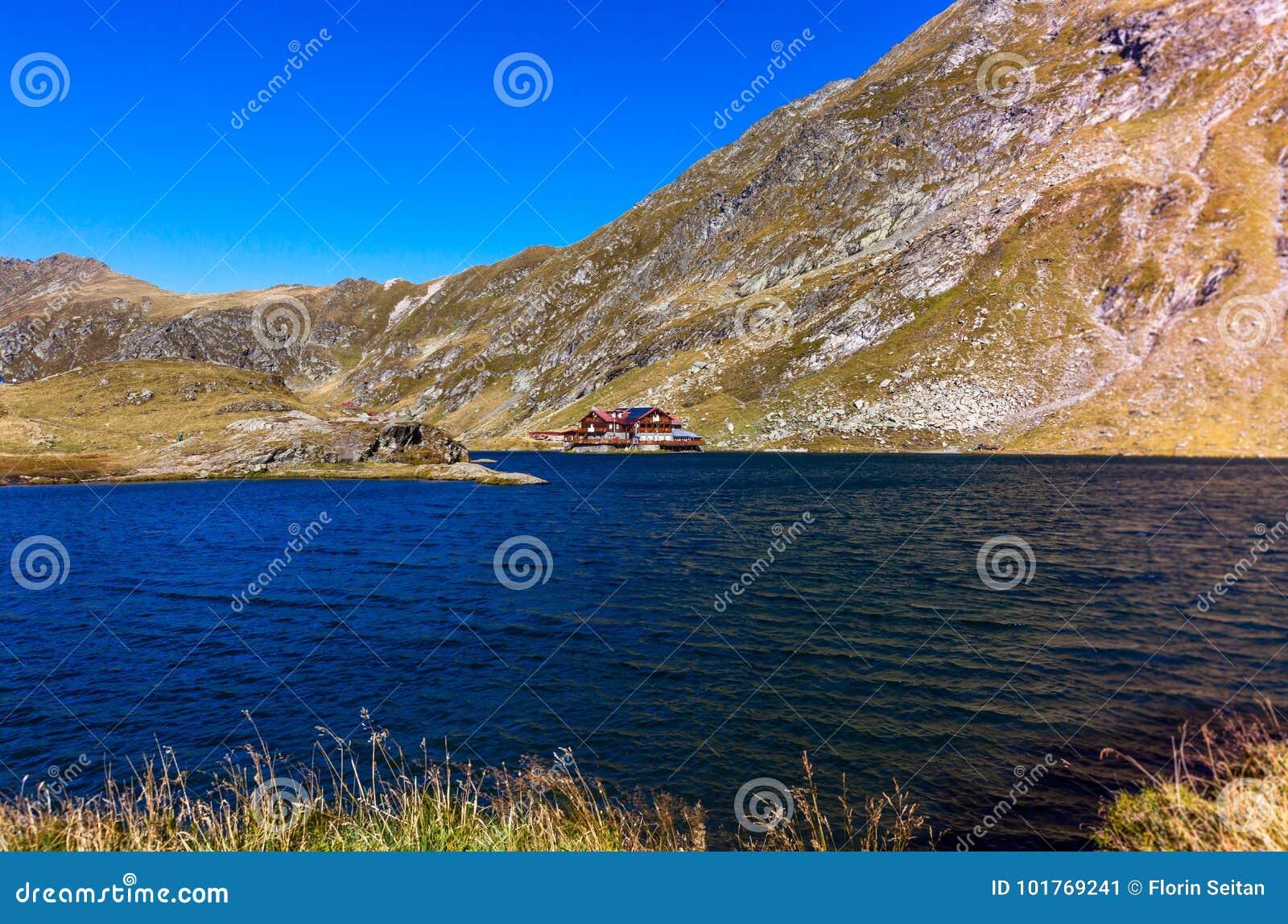 Balea sjö i de Carpathian bergen, röd kabin vid sjön