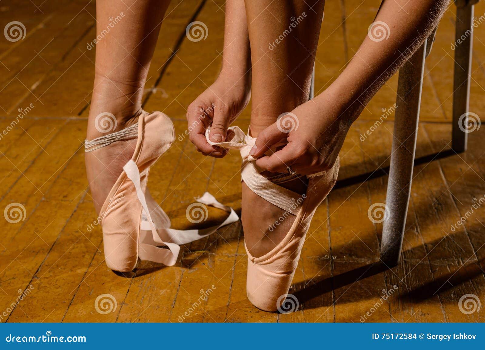 Balerina wiąże pointe baletniczych buty na scenie