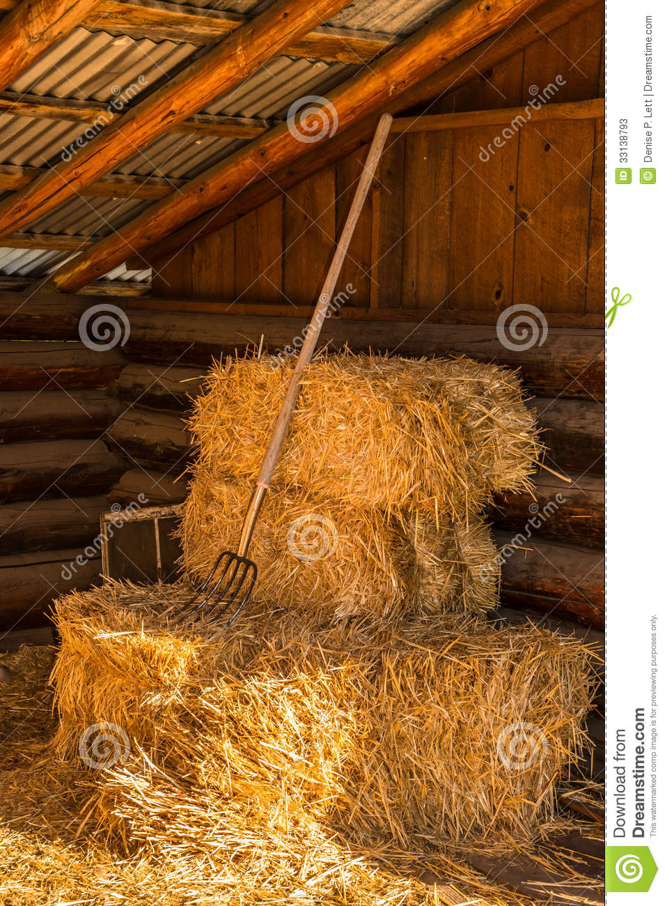 Bales Of Straw Hay With Pitchfork In Barn
