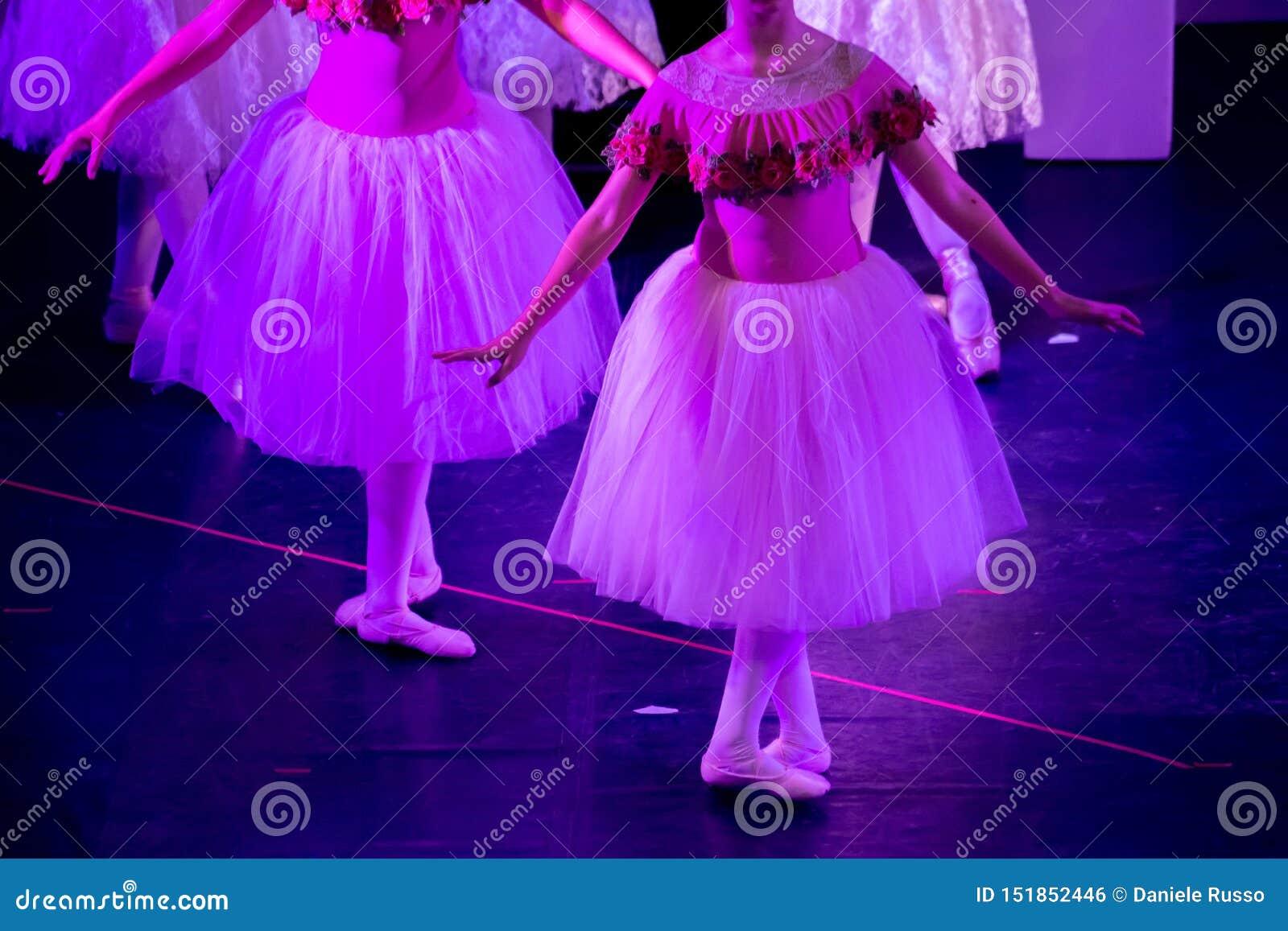 Balettdansörer under purpurfärgat ljus med klassiska klänningar som utför en balett på suddighetsbakgrund