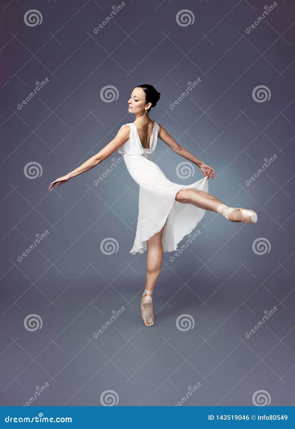 Balettdansare-ballerina på punktskor med en vit klänning