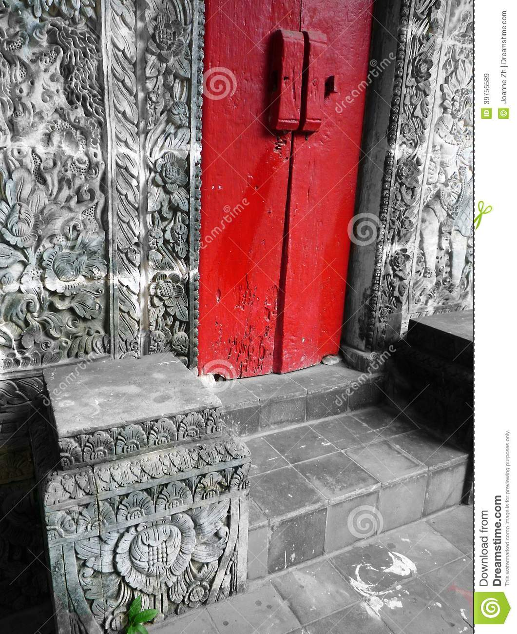 Bali house with red door stone carved walls stock image
