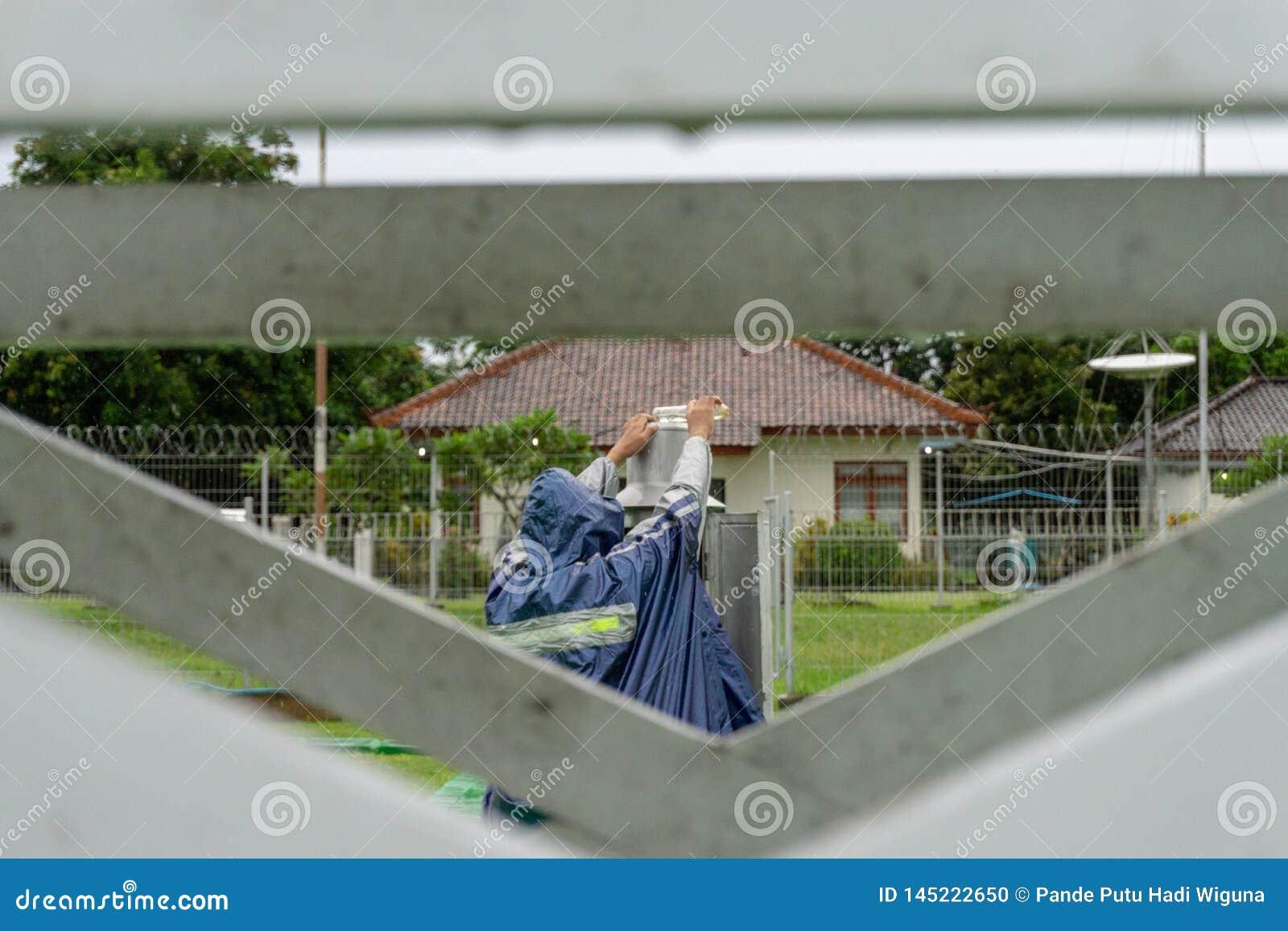 BALI/INDONESIA- 21 DÉCEMBRE 2017 : Un observateur météorologique vérifie le mètre de pluie de Helman au jardin de météorol