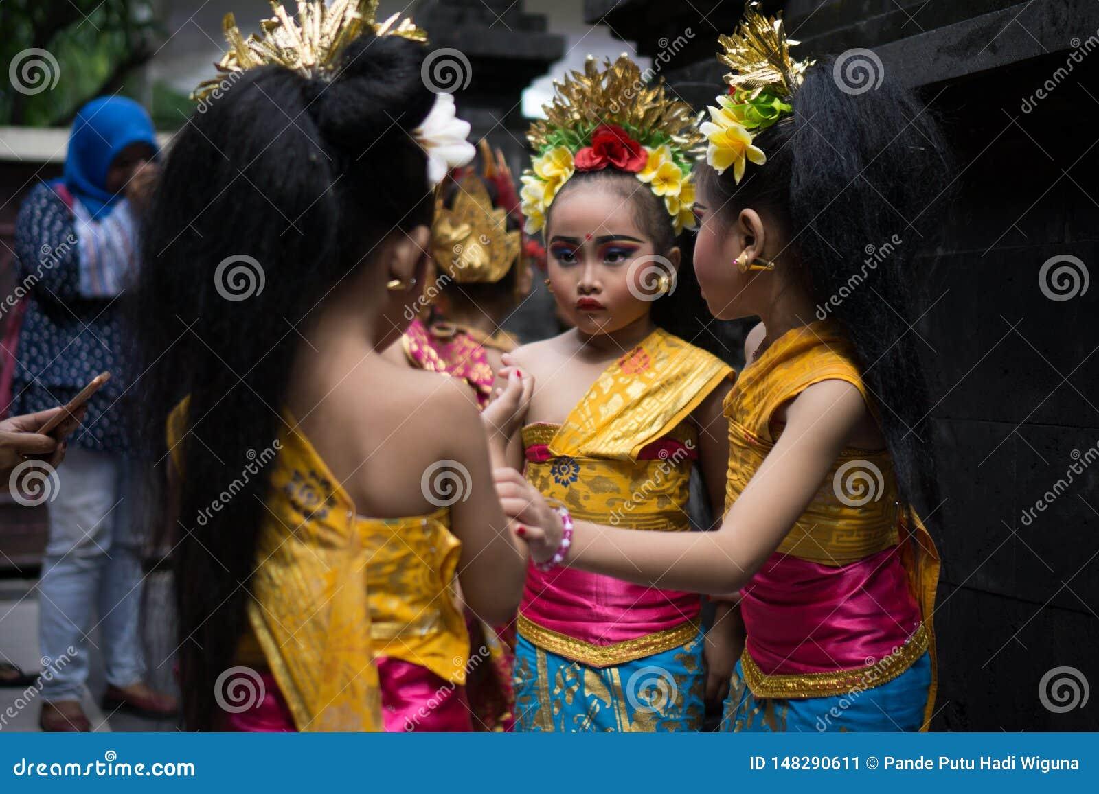BALI/INDONESIA- 28 DE DEZEMBRO DE 2017: Tr?s dan?arinos novos do Balinese que vestem a roupa tradicional do Balinese e comp?em, e