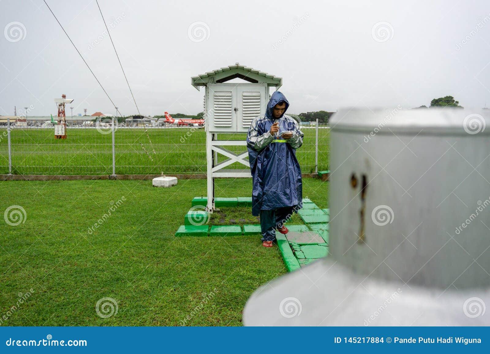 BALI/INDONESIA-DECEMBER 21 2017: En meteorologisk observatör kontrollerar den meteorologiska buren på meteorologiträdgården f