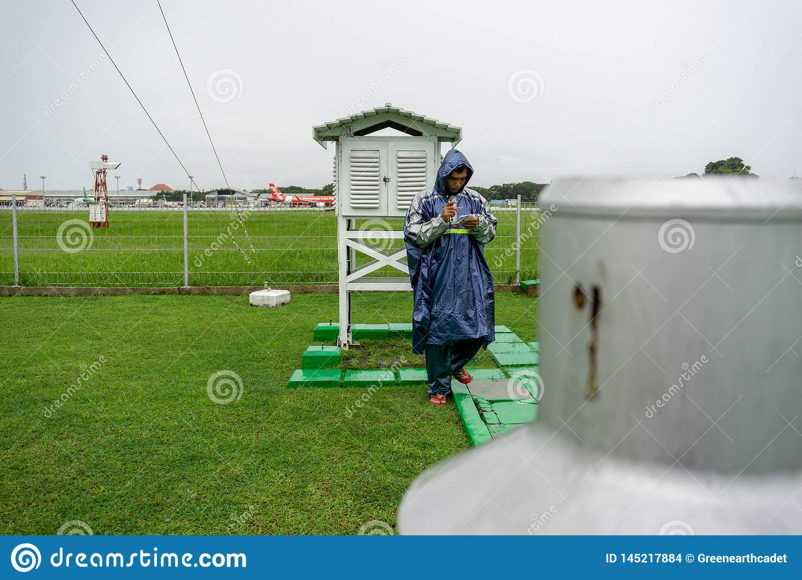 BALI/INDONESIA-DECEMBER 21 2017: Meteorologiczny obserwator sprawdza meteorologiczną klatkę przy meteorologia ogródem upewnia