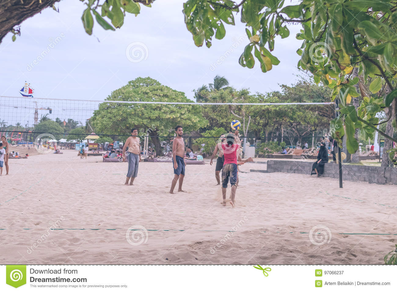 BALI, INDONESIA - JULY 27, 2017: Group of friends playing beach volley - Multi-ethic group of people having fun on the