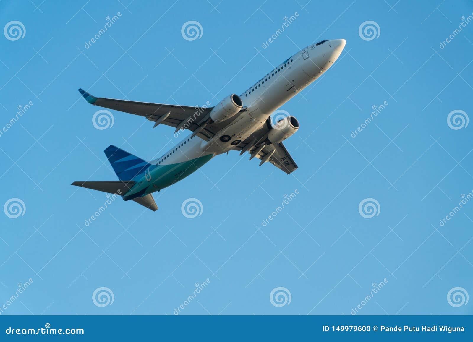 BALI/INDONESIA-JUNE 06 2019: Garuda Indonesia, jeden linie lotnicze które łączą niebo drużyny w Indonezja, lata nad błękitem