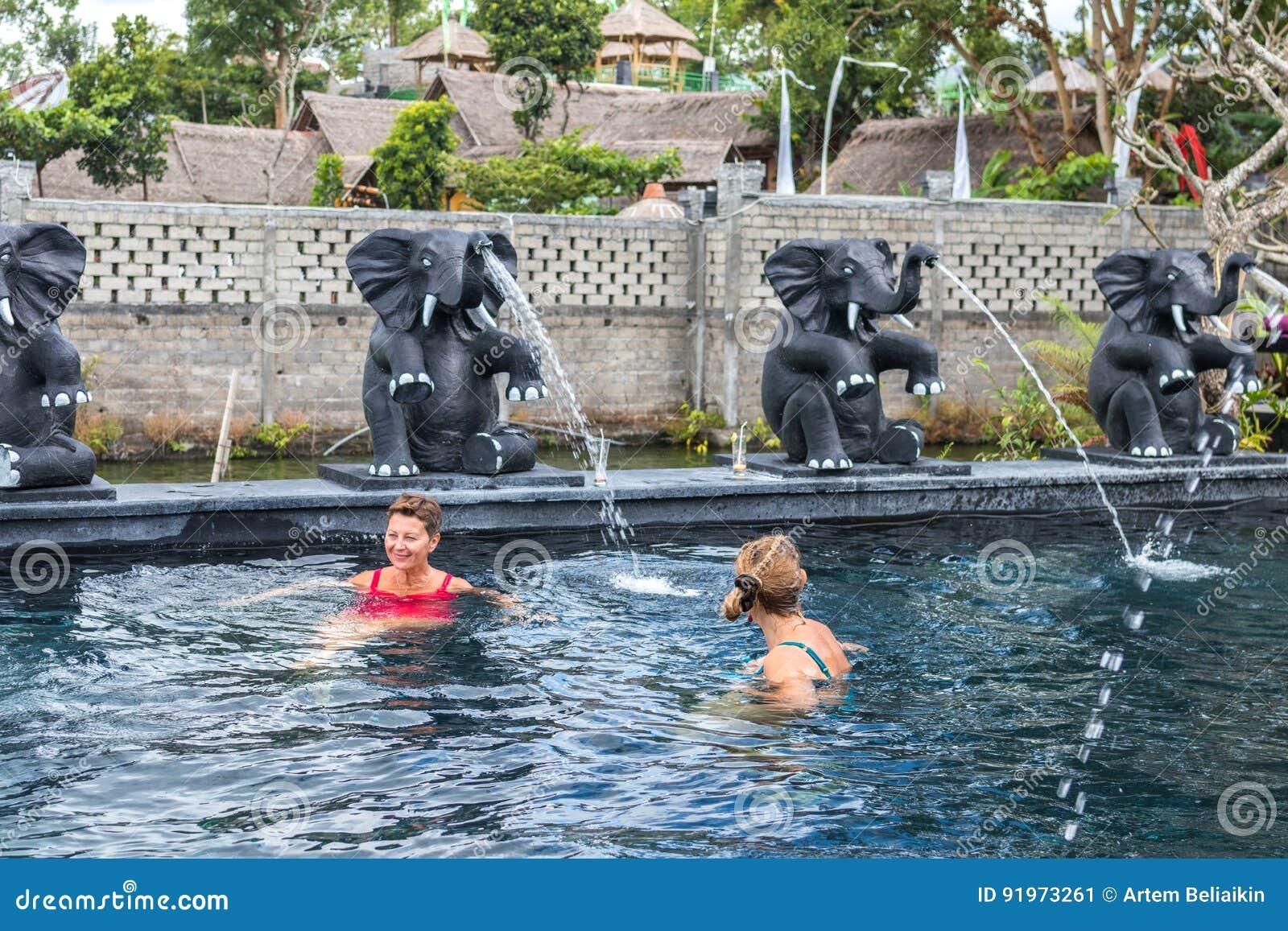 BALI, INDONESIA - 5 MAGGIO 2017: Due donne senior in buona salute che nuotano nella piscina della natura Stile di vita attivo bal