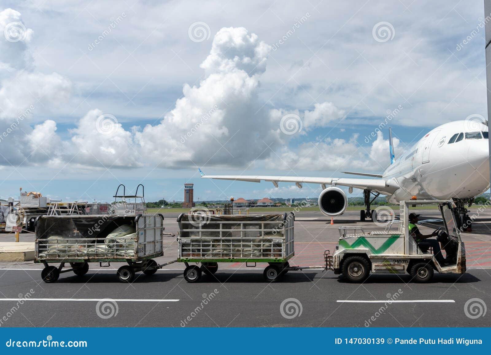 BALI/INDONESIA-MARCH 27 2019: Lotniskowi pojazdy ciągną pasażerów bagażowych przyjazdowy śmiertelnie gdy słoneczny dzień z cumulu